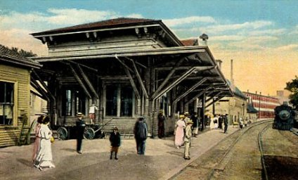 "Amesbury passenger station viewed from Water Street around 1900. Hand-colored postcard from ""Railroad Stations in New Hampshire and in Massachusetts"" (lightlink.com/sglap3)."