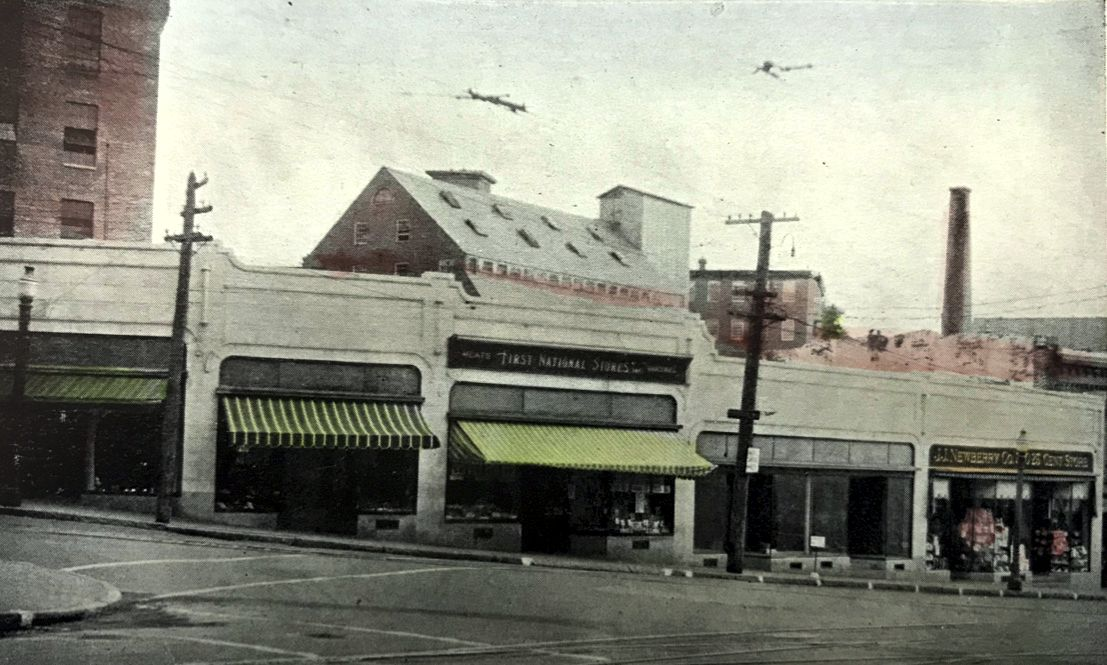 Ca. 1940 view of the Main and Friend Street storefronts. A portion of Mill 8 is visible in the upper left.