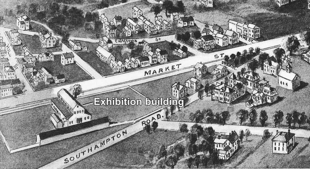 Fair grounds with exhibition building and cattle shed in a 1914 aerial view.