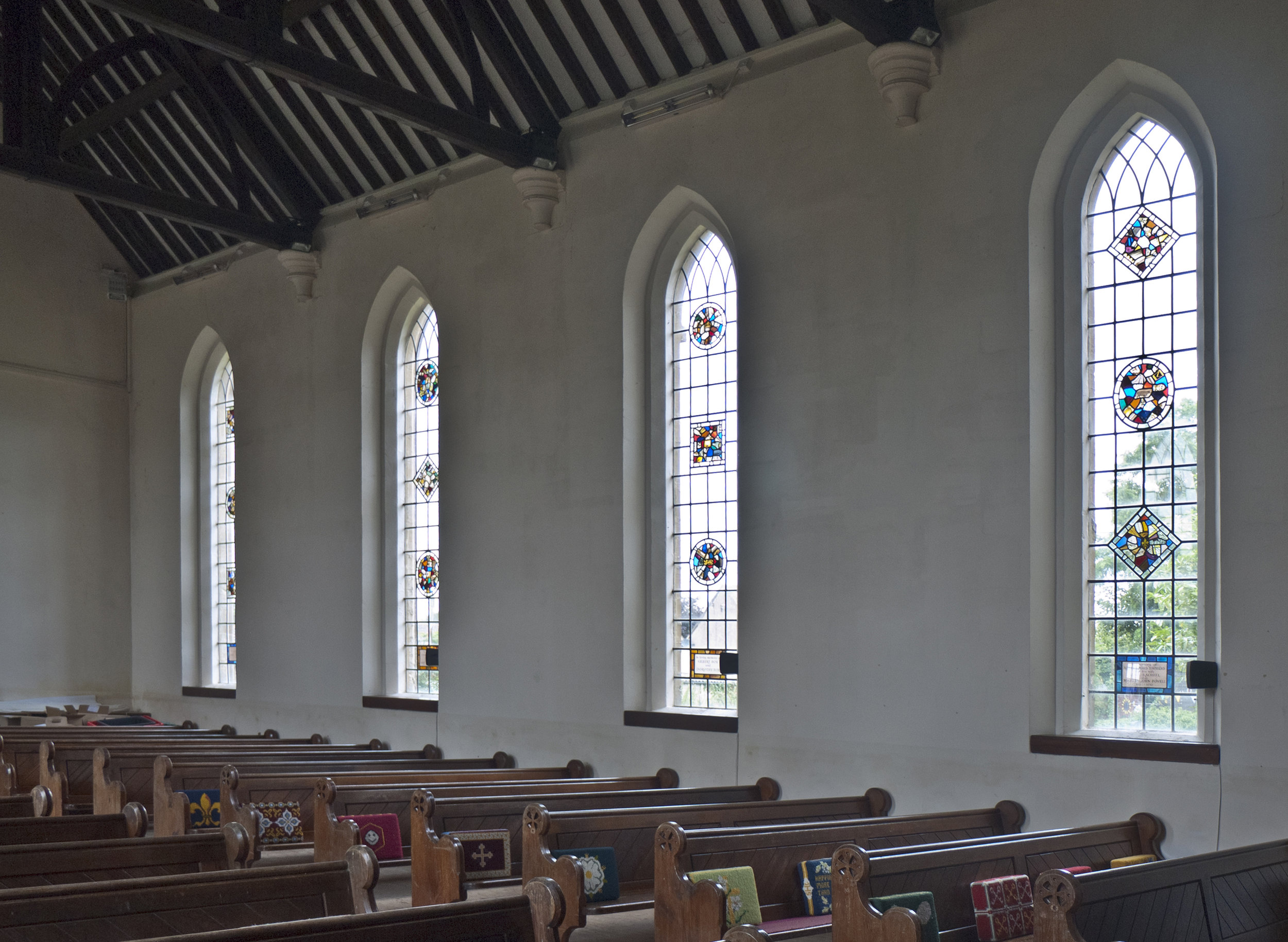 Inside the nave, plain apart from glass medallions, kneelers & pews - all very attractive.