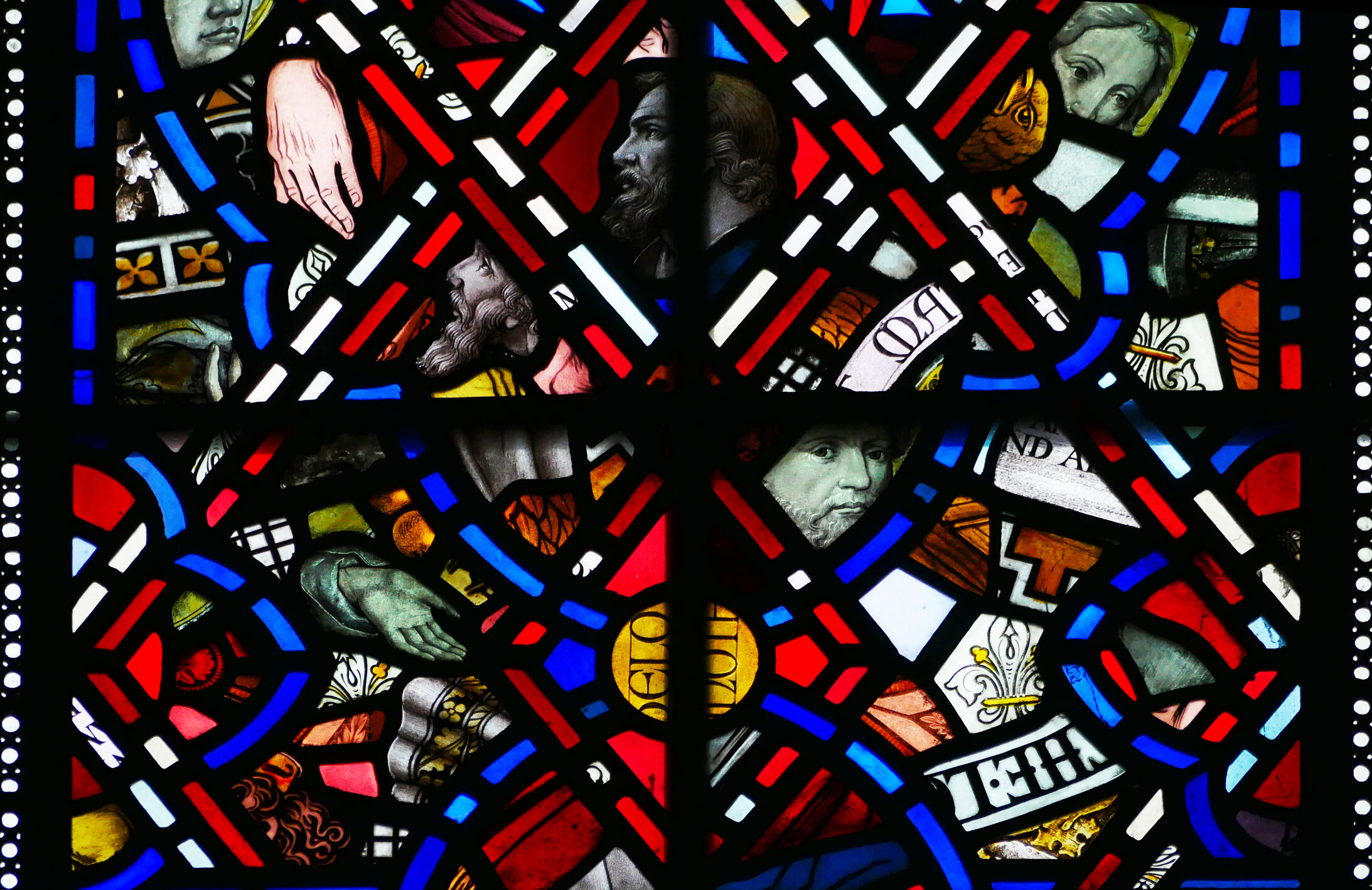 Detail from the third window above the altar with expertly arranged fragments and faces.