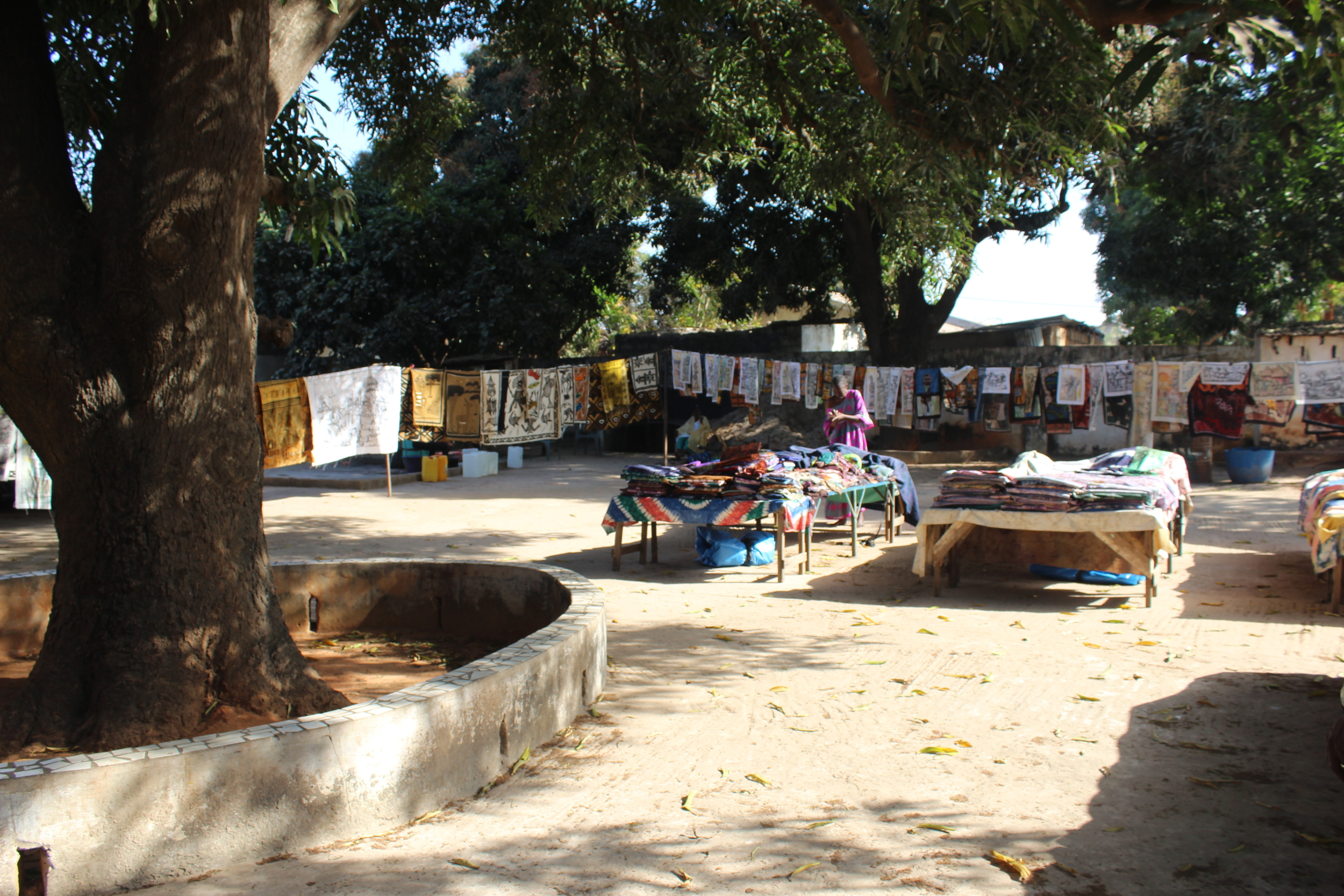 Artwork hung out to dry under a large Mango tree. The central tables contain hundreds of folded and ironed fabric or handmade finished items such as tablecloths and bedding sets.