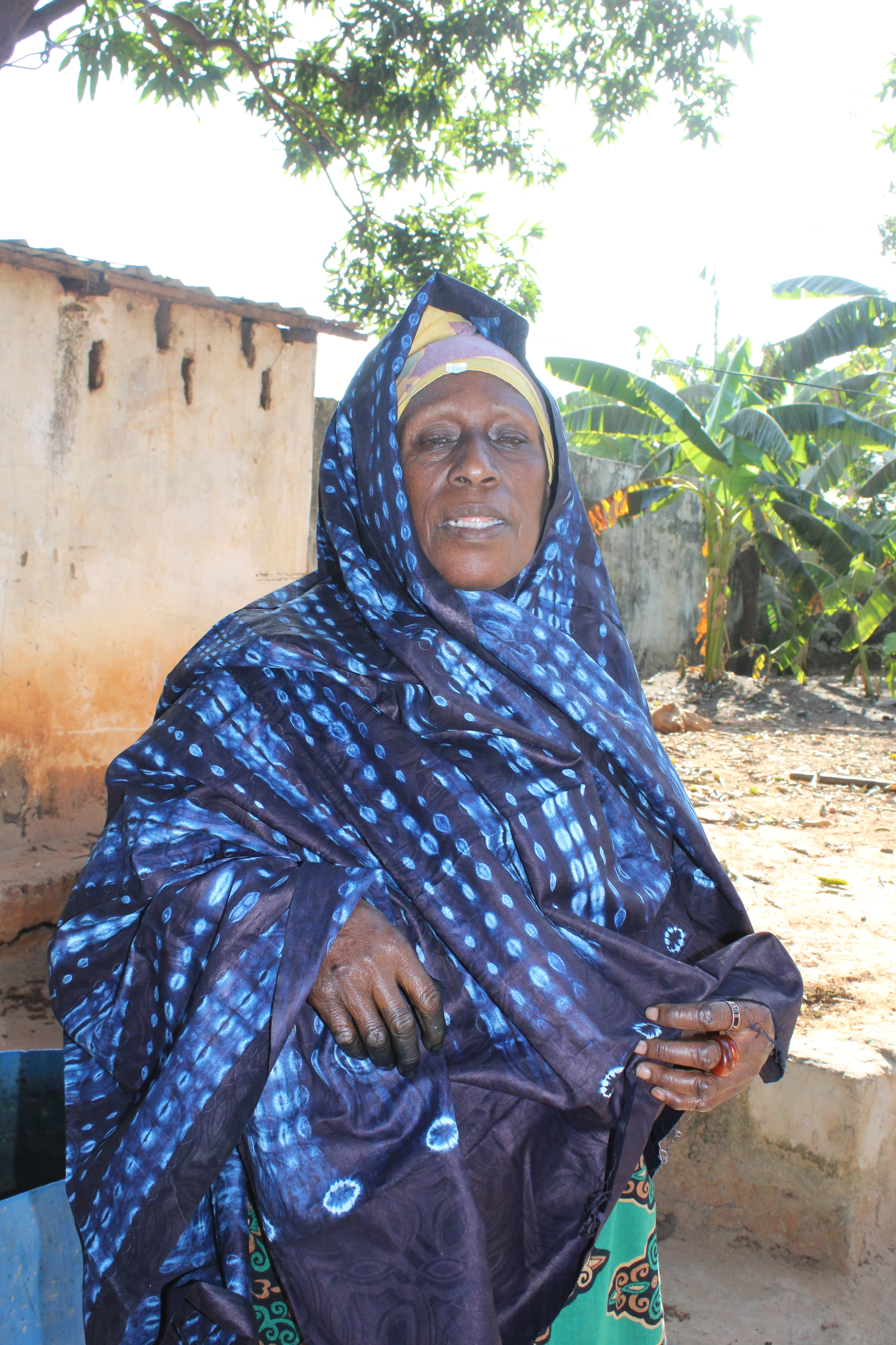 Nafri (sp) the matriach expertly models a piece of finished tie dyed indigo cloth, her own handiwork. Usually worn as a skirt.