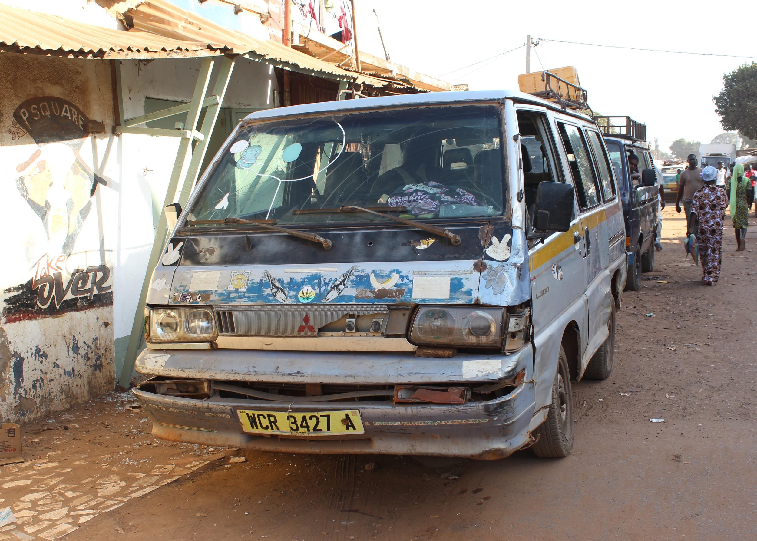 Battered but beautifully decorated passenger van.
