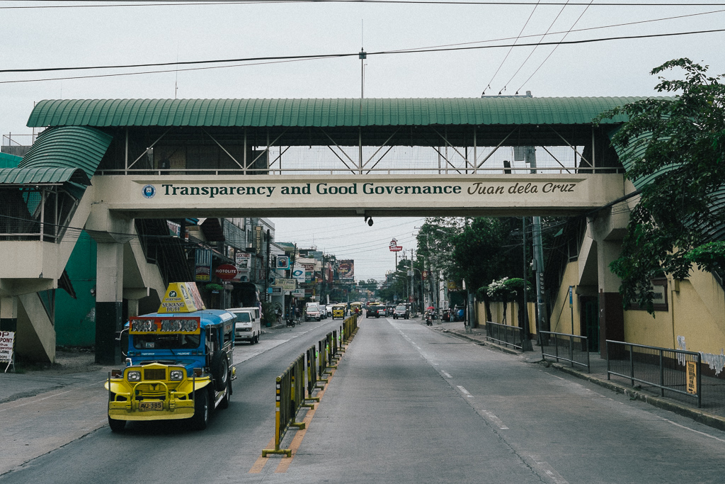 A main road in Olongapo with the city's motto on a pedestrian overpass.