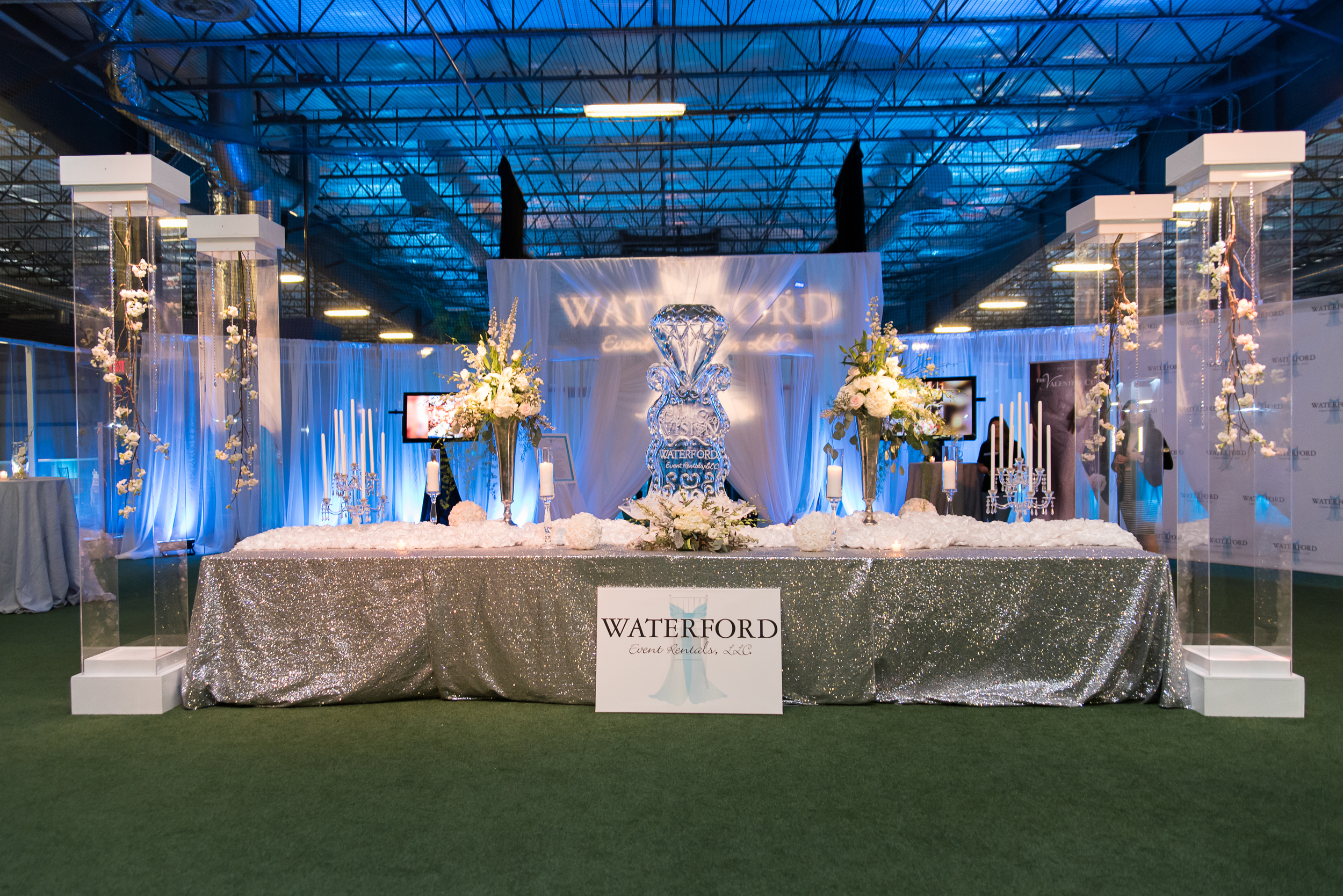 Design and linens by Waterford Event Rentals. Florals and columns by Botanique. Ice sculpture by Ice Art. Uplighting by Blue Steel Lighting Design.