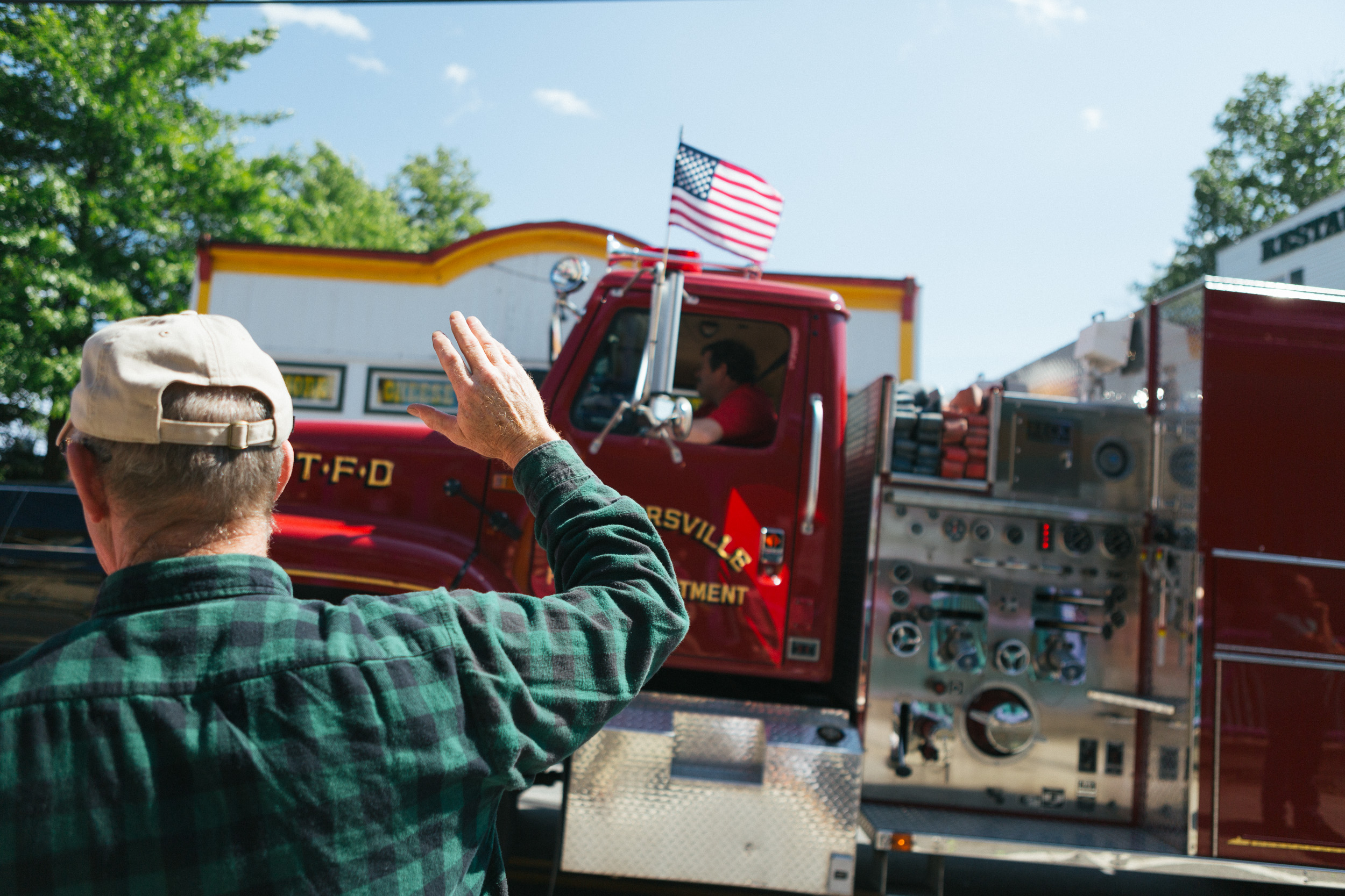A man waves to the passing trucks at the Tannersville Fourth of July Parade.jpg