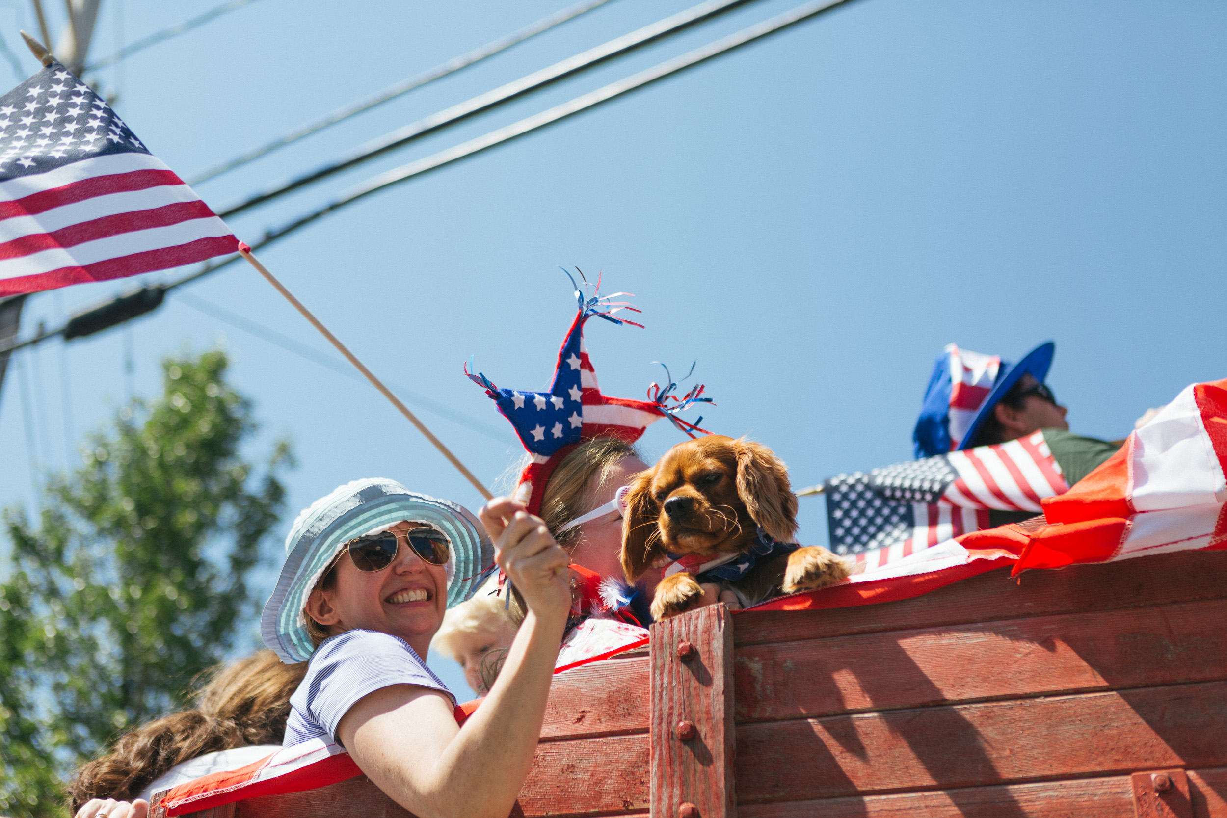 A woman waves a flag as her puppy hangs from the side of a float at the Tannersville Parade.jpg
