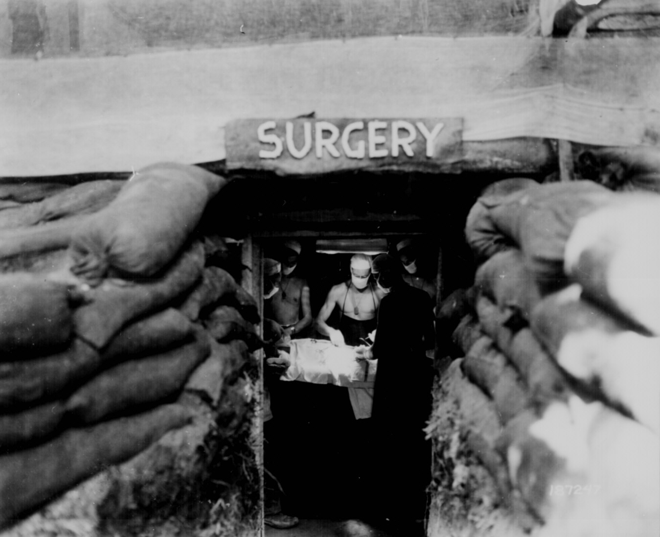 In an underground surgery room, behind the front lines on Bougainville, an American Army doctor operates on a U.S. soldier wounded by a Japanese sniper.  12-14-1943