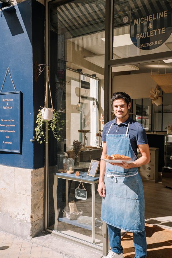 """Valentin, pâtissier at """"Pâtisserie Micheline et Paulette"""" on Rue Notre Dame, holding a banana cake."""