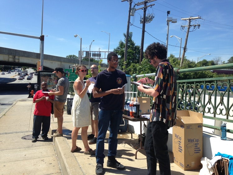 Volunteers and RHIC staff talk to passersby at the summer snowball stand about their ideas for a new West North Avenue Streetscape.