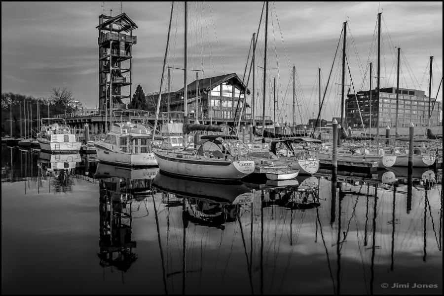 A black and white photograph of boats are seen on the glass-slick water of a busy harbor in Baltimore.
