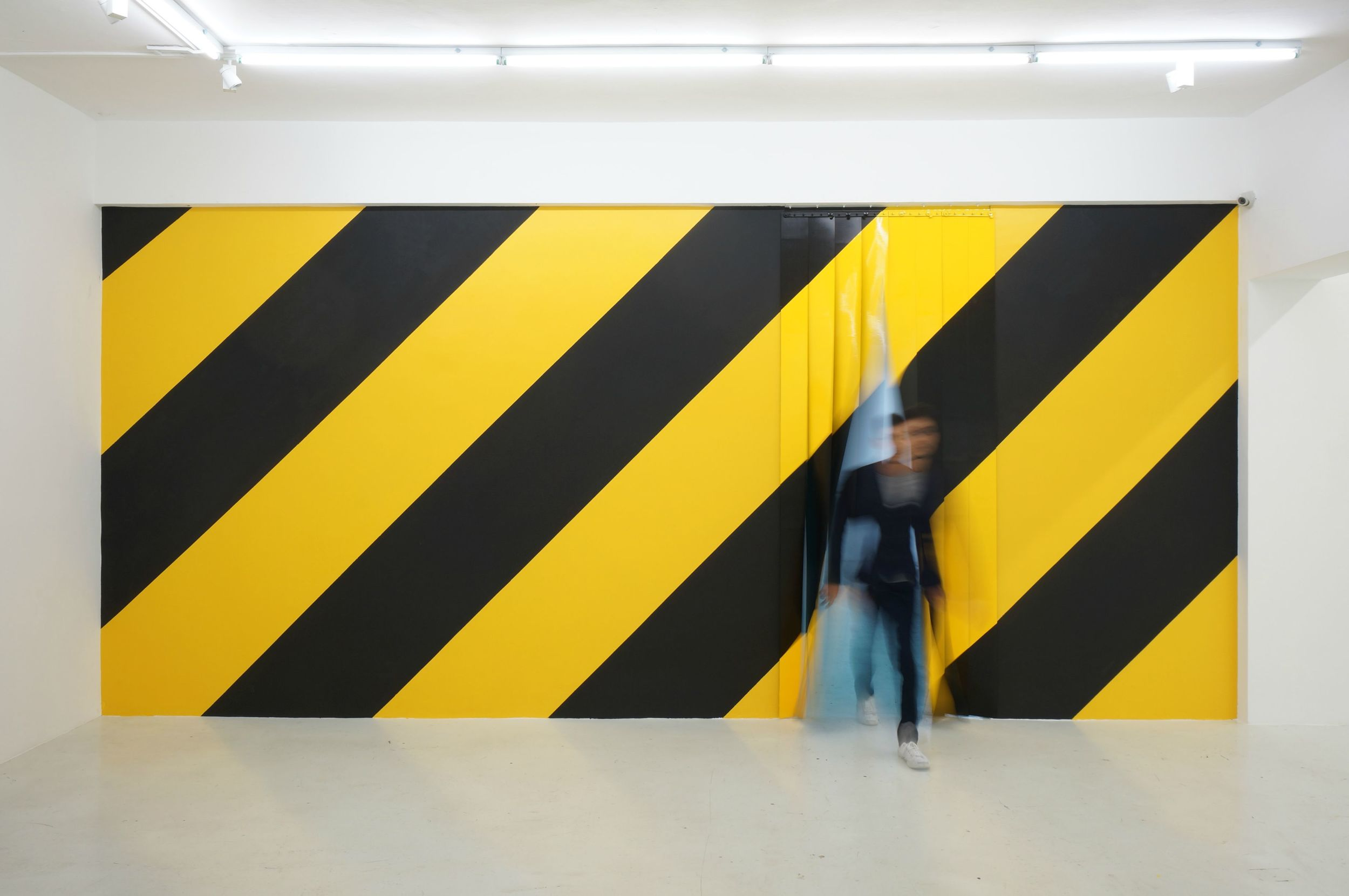 Michael Lee,  Diagonals  (installation view with the artist), 2014.   Emulsion on wall, polyurethane on PVC and enamel on galvanised iron, 294 x 650 cm.   Yavuz Fine Art, Singapore. Photo by Ken Cheong.