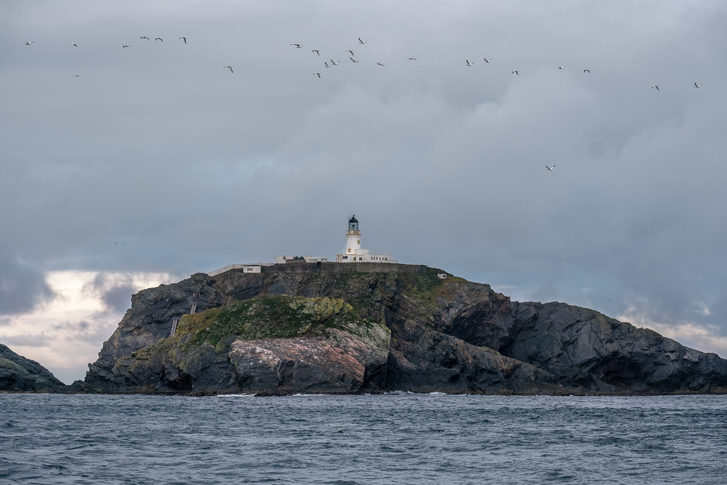 Northernmost point in the UK. If you look closely to the left of the lighthouse you can see two ladders on the side of the island. Climbing these plus the lower one you cant see is the only way to get to the lighthouse from a boat for people and supplies.