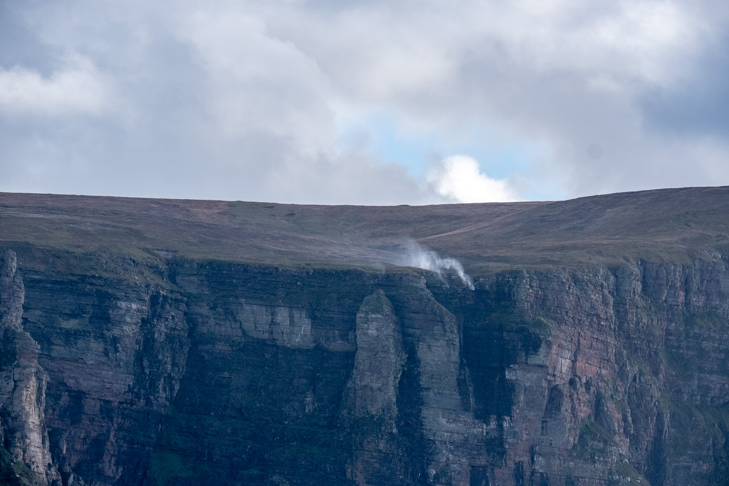 White smoky patch is not smoke but a waterfall, which with Force 8 gale winds is being blown in reverse back up the waterfall
