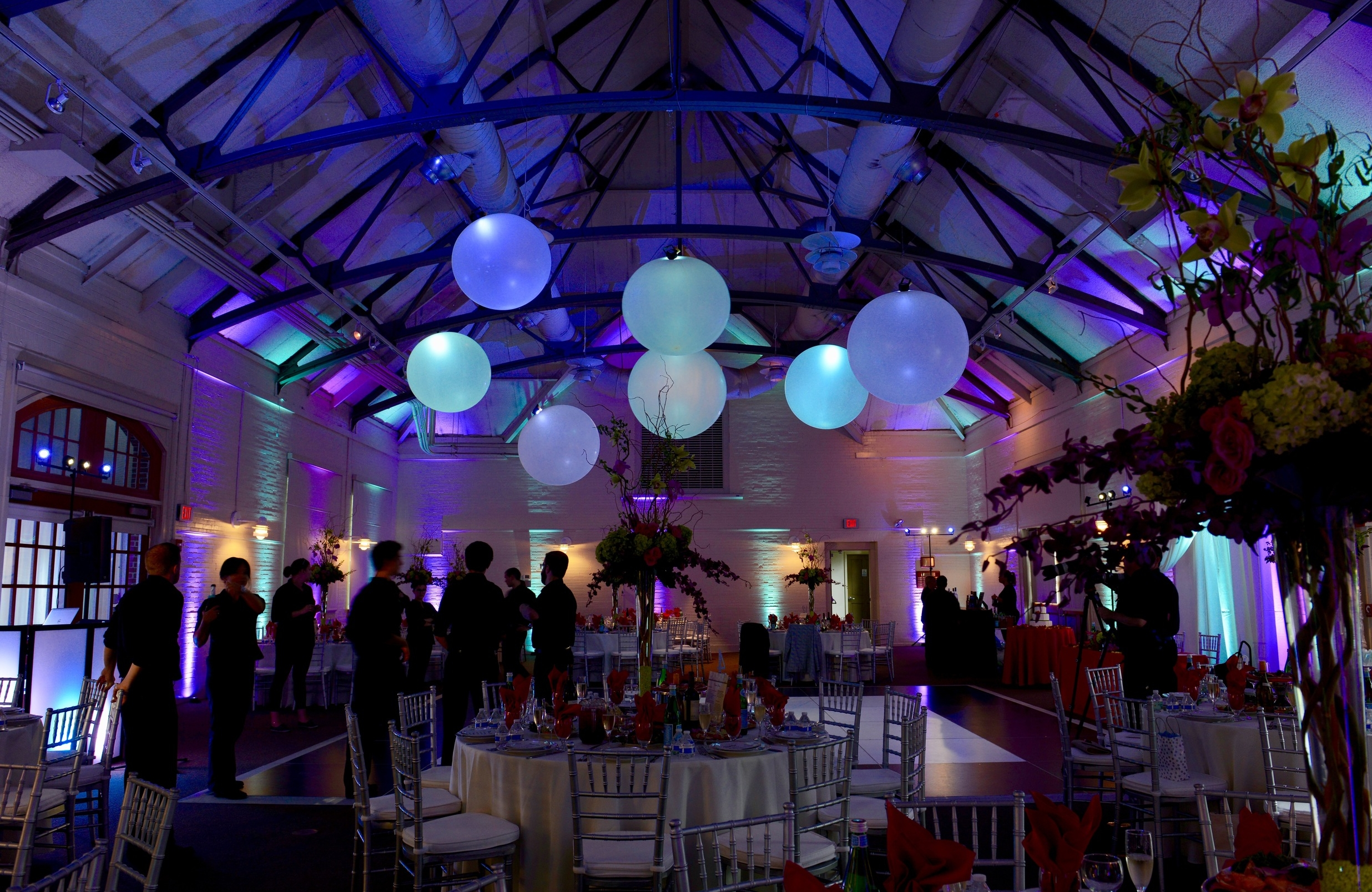 The guests entered a room of teal and purple.   Warm light around the room was kept at the level of the tables to illuminate them separately but not brightly so as not to lose the effect of the colored light.