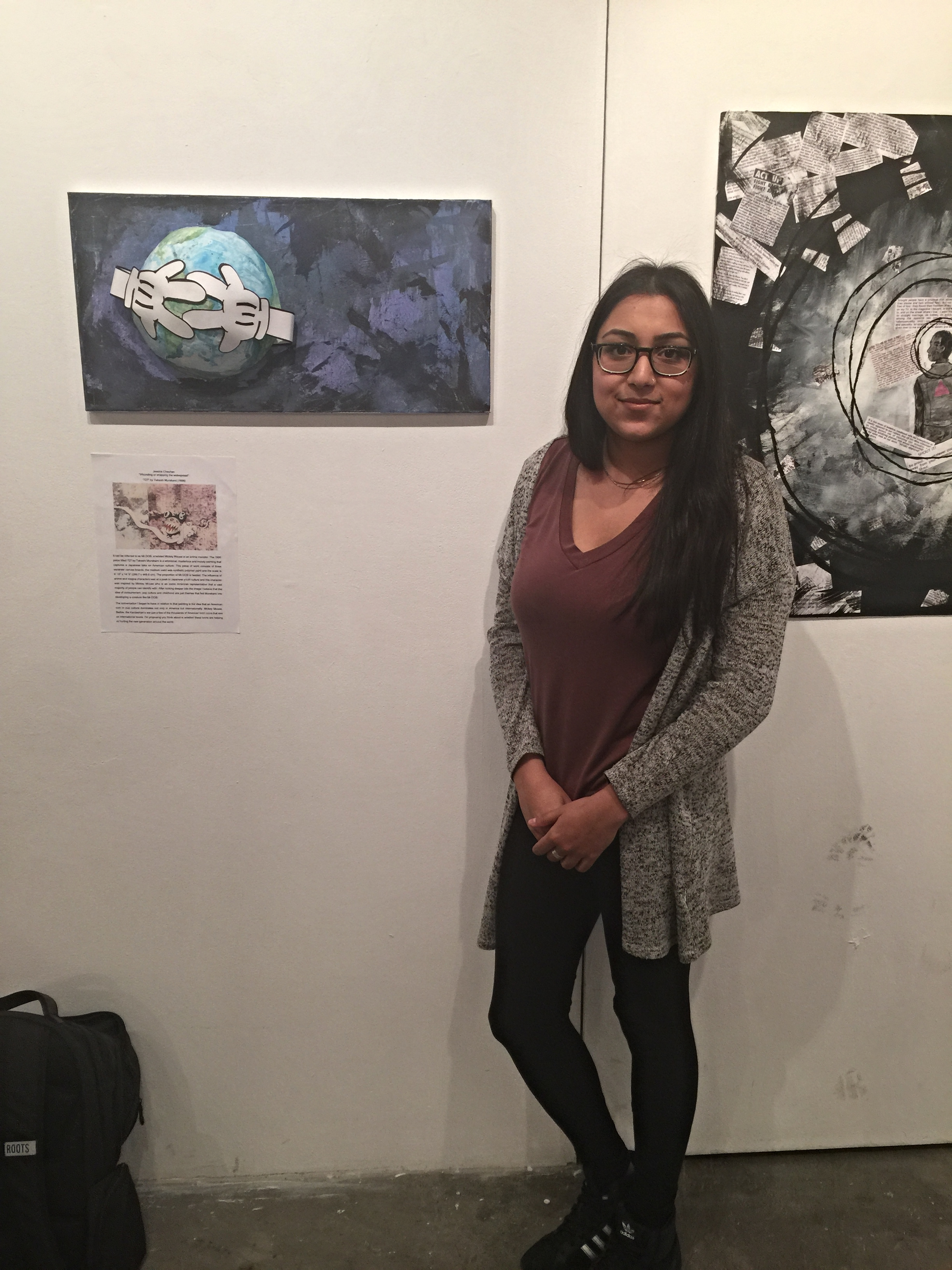 """Jessica standing with the art work she exhibited at KPU as part of the """"Talking Back"""" exhibition ahead of the trip portion of the field school."""