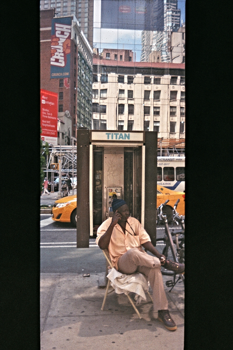 Around every corner in New York... Andi capturesan unexpectedmoment and juxtaposition. A street vendor talking on his cellphone inside a phone booth.