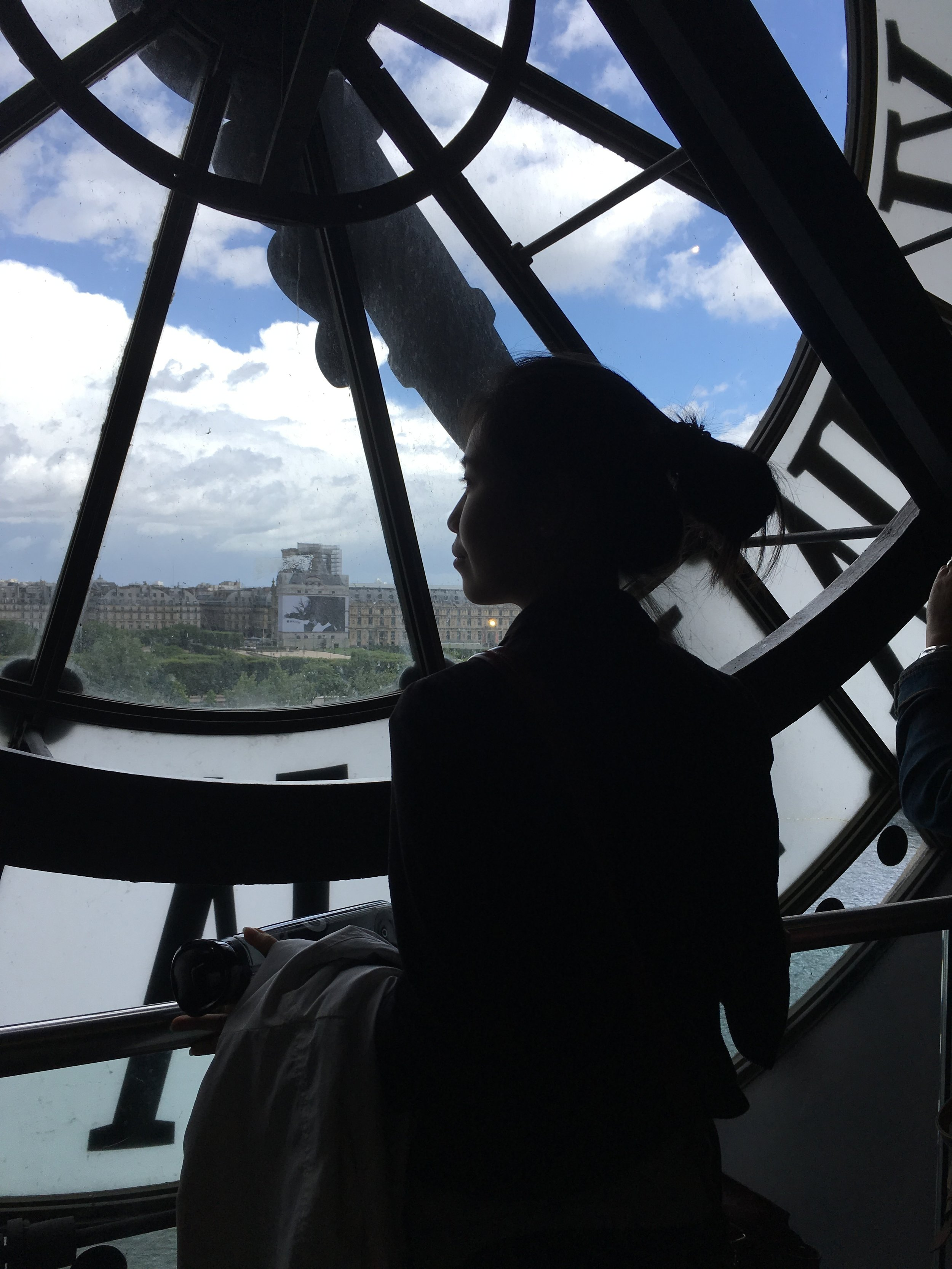Alice in silhouette looking out onto to the Seine river towards the Louvre from the behind the famous Orsay clock.