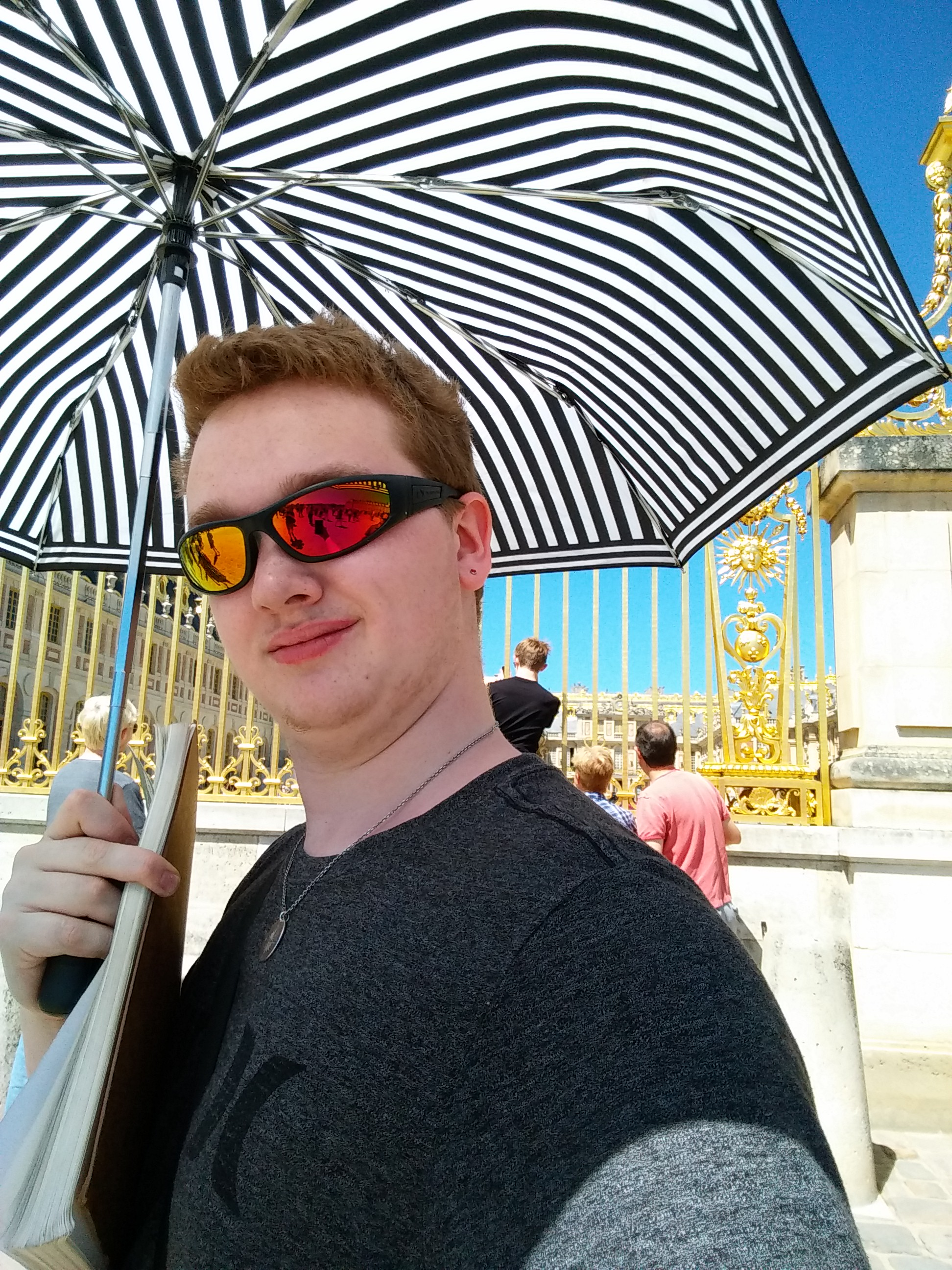 Cameron shielding himself from the hot French sunshine at the Palace of Versailles.