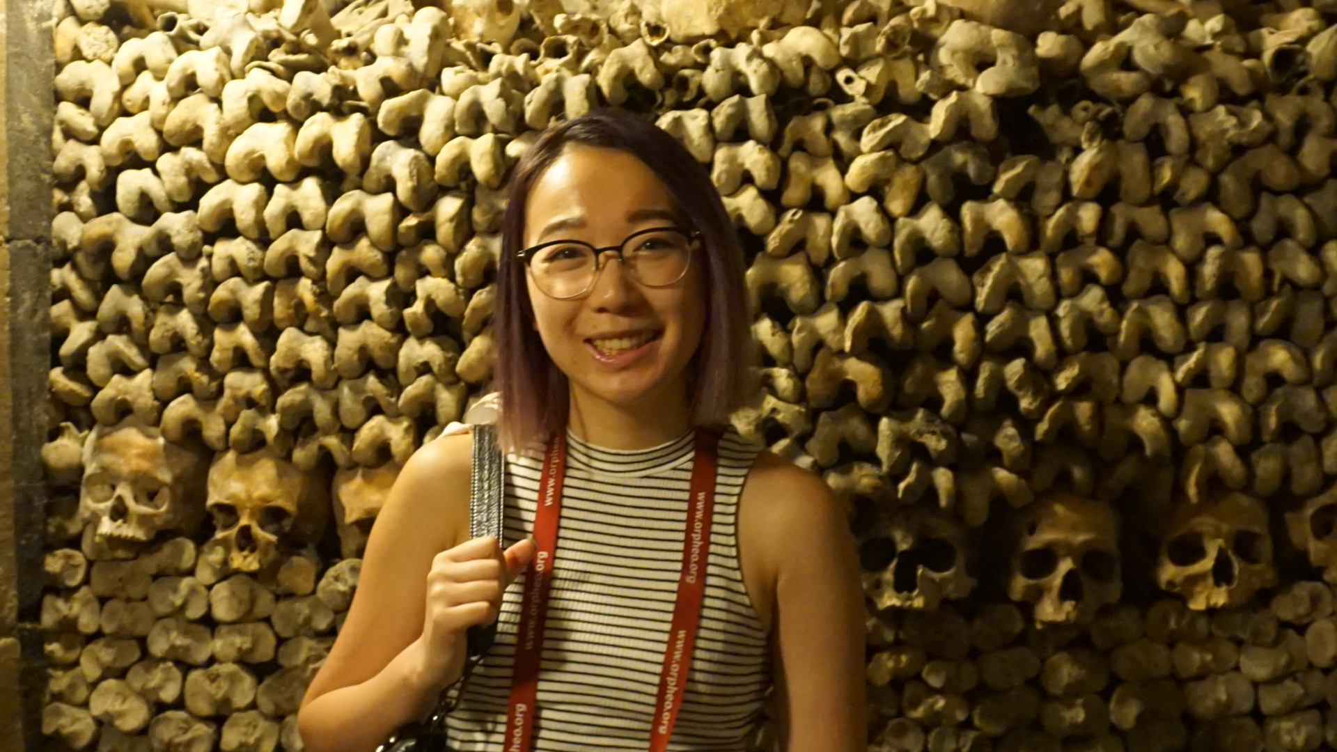Jenny standing in front of human skulls and bones found in the Paris catacombs.