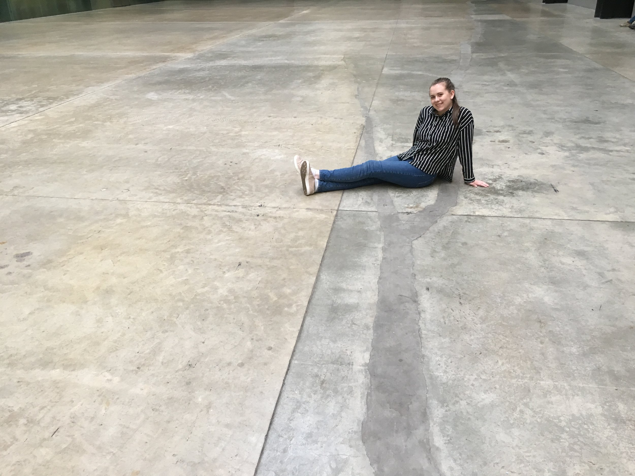 Alison pictured in the Tate Modern's Turbine Hall sitting on the scar left behind by Doris Salcedo's large scale project  Shibboleth II  (2007).