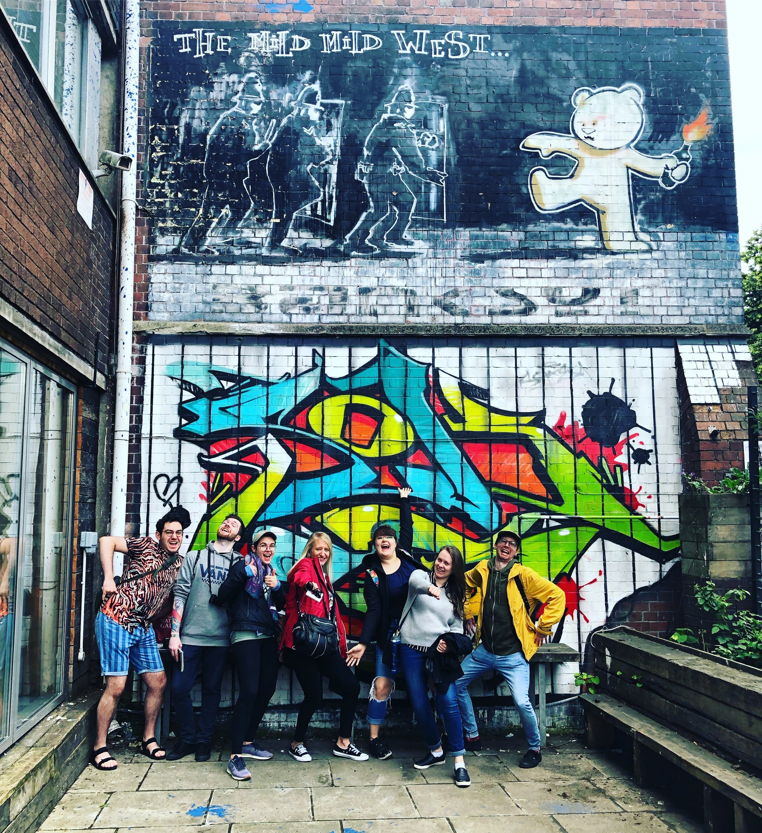 The trip to Bristol was a day to remember. Pictured left to right in front of the oldest public Banksy work in Bristol:: Adam, Steven, Leah, Dorothy, Victoria, Alison, and Mark.