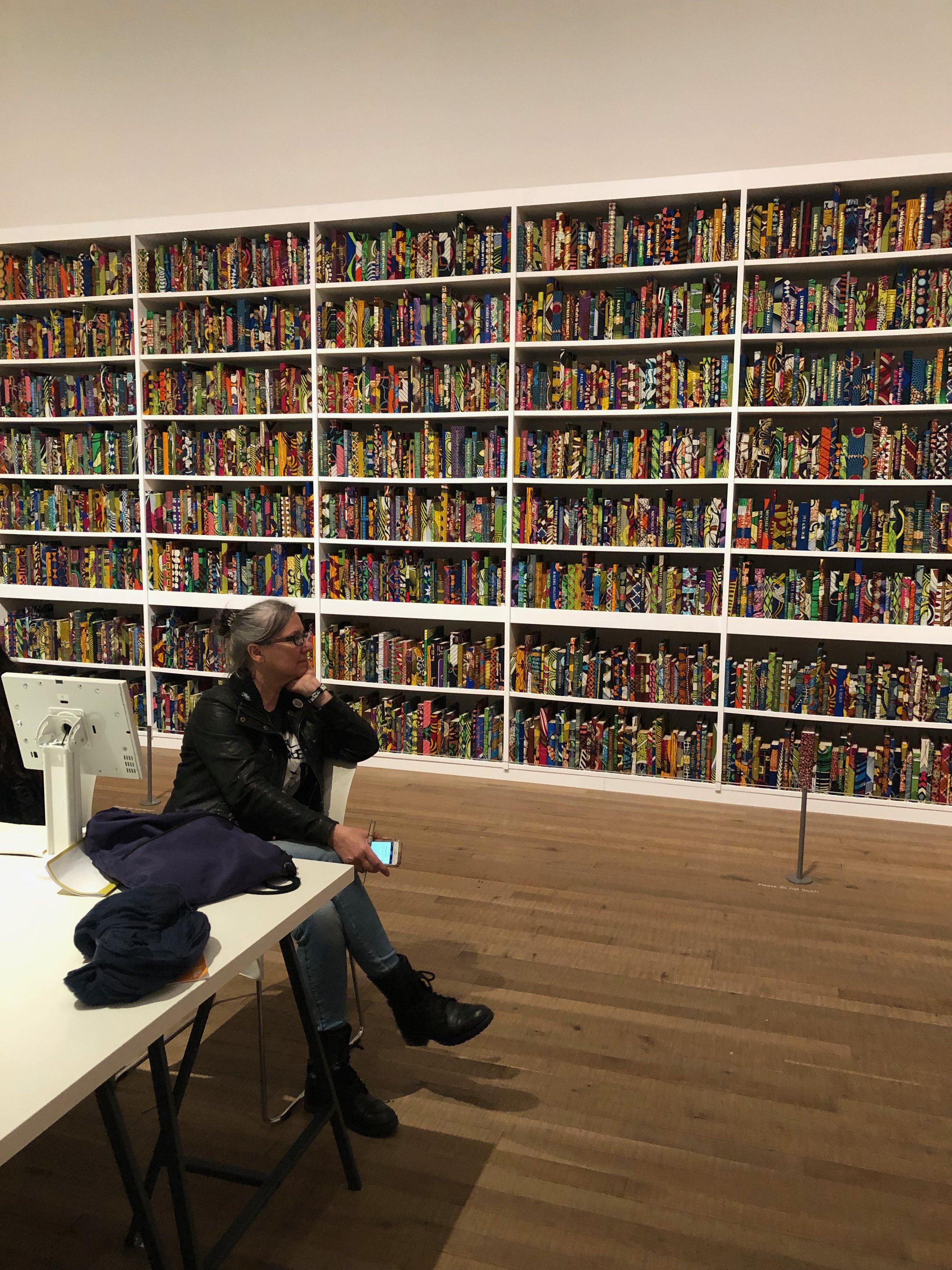 Angela sitting and enjoying her assigned artist's installation at Tate Modern— Yinka Shonibare's  British Library  (2014)