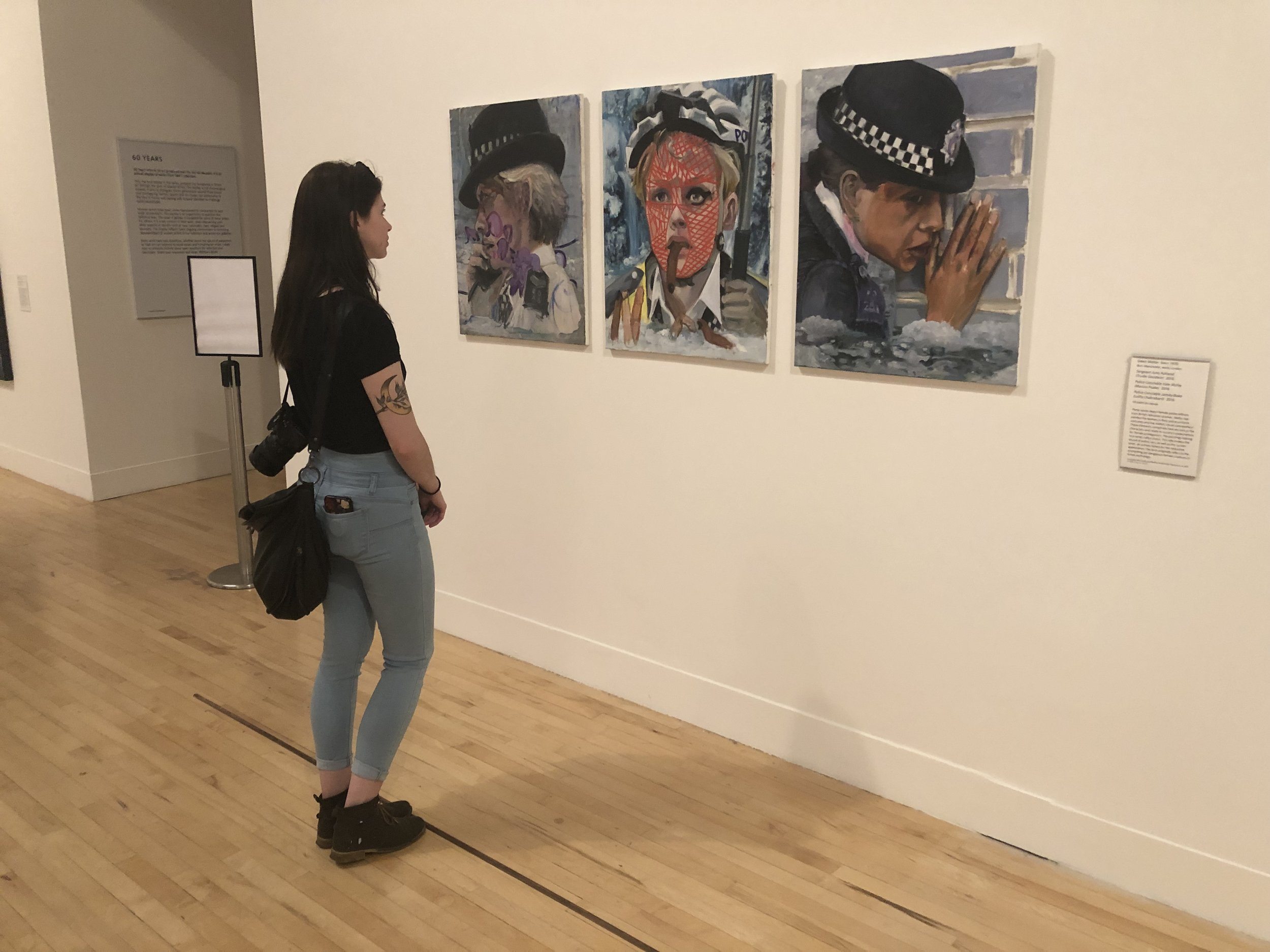 Meg looking at another of her assigned artists at Tate Britain—  Dawn Mellor's  Police Constable Kate McFay (Maxine Peake)  (2016)