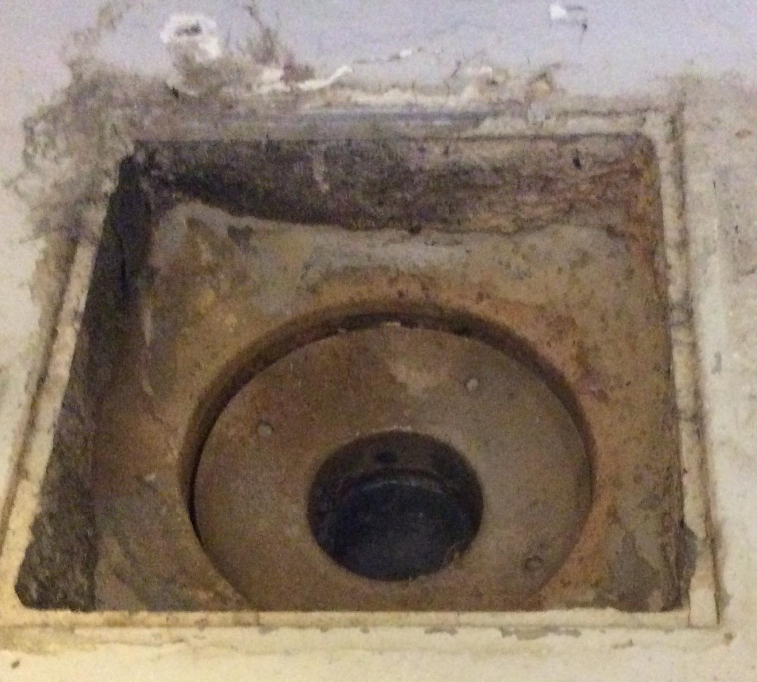 Eksempel på et gammelt gulvafløb, hvor siderne er af beton. Går du ikke med renoveringsplaner, er det vigtigt at der på intet tidspunkt er et tilstoppet afløb, da dette vil gøre at vandet stuves op og får direkte kontakt til beton. Løft risten for at tjekke det.