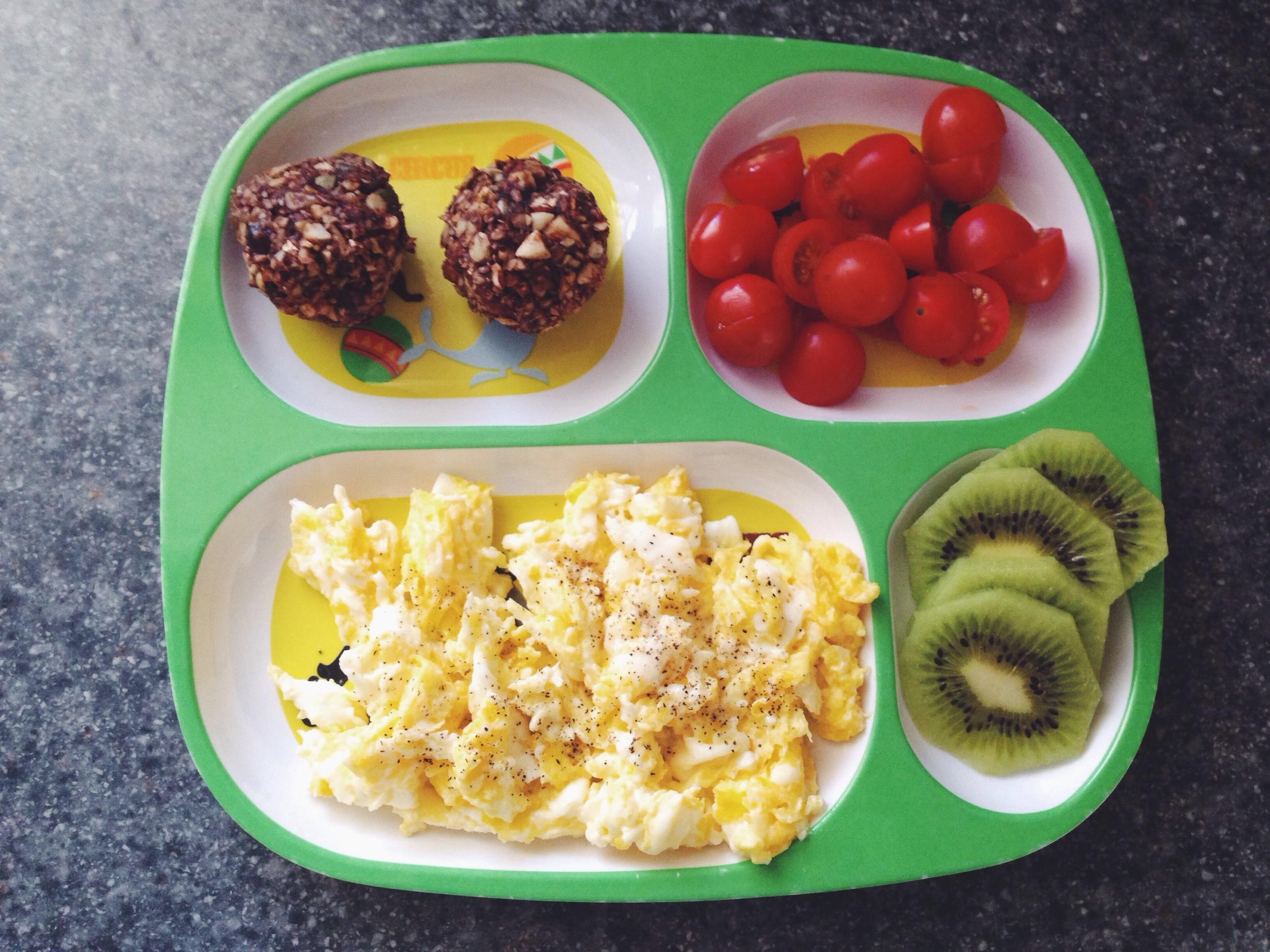 """energy bites"" / cherry tomatoes / scrambled eggs / kiwi slices"