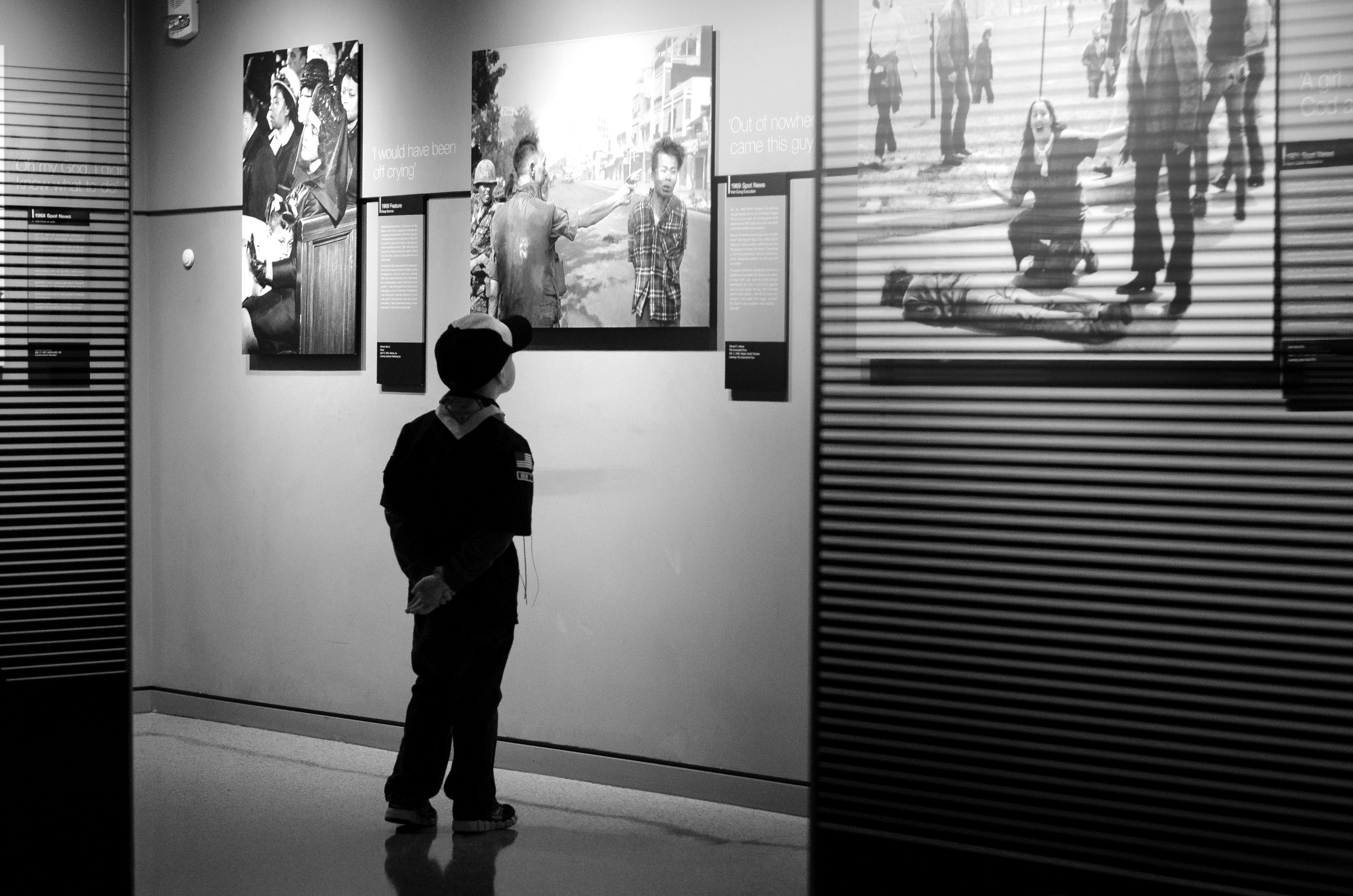 A Cub Scout looks up at a Pulitzer Prize winning image from the Kent State shooting at the Newseum in Washington, D.C.