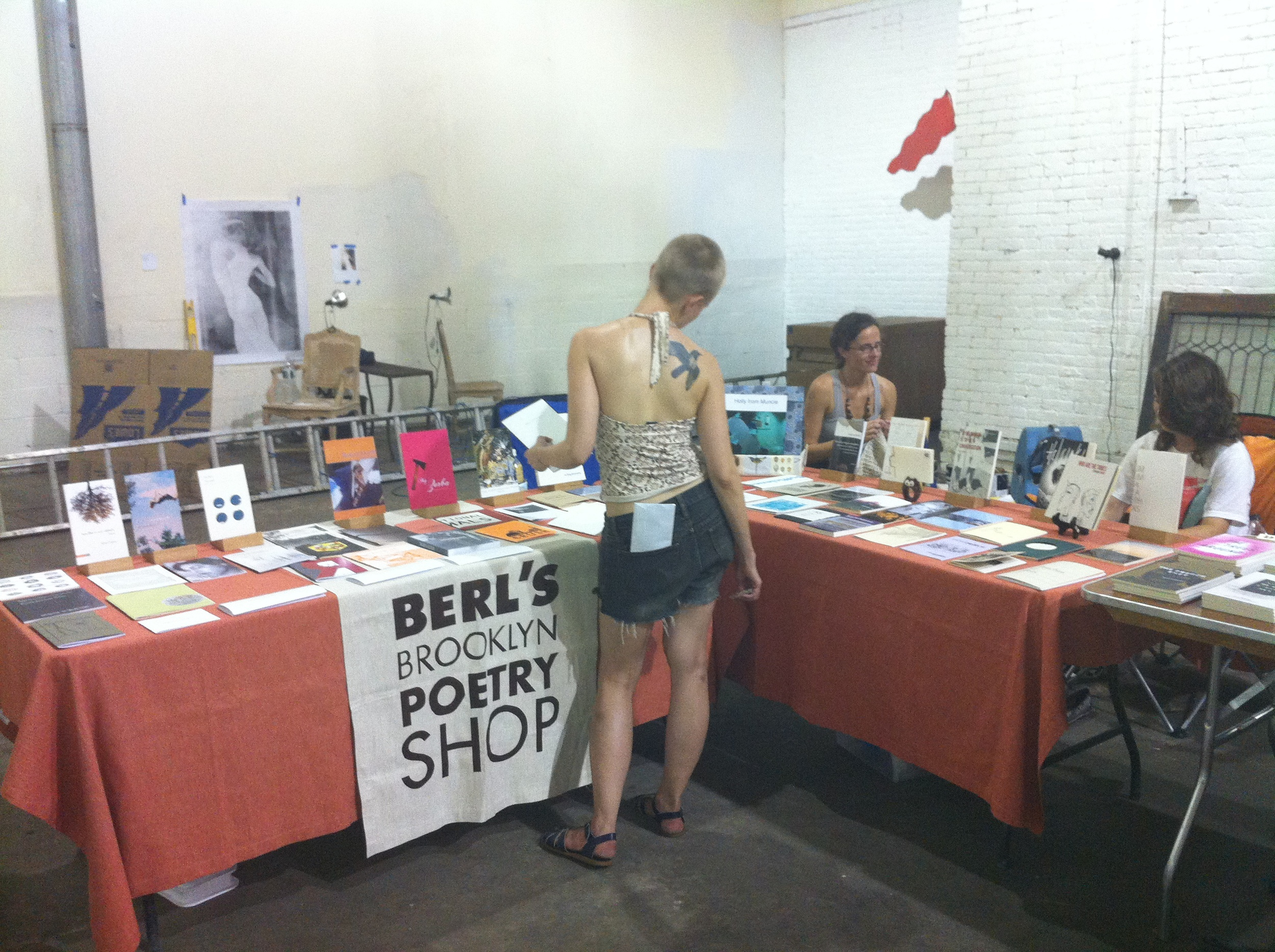 Popsickle Poetry Festival founder Niina Pollari peruses books at Berl's pop-up booth, including MY ZORBA by Danielle Pafunda (Bloof Books).