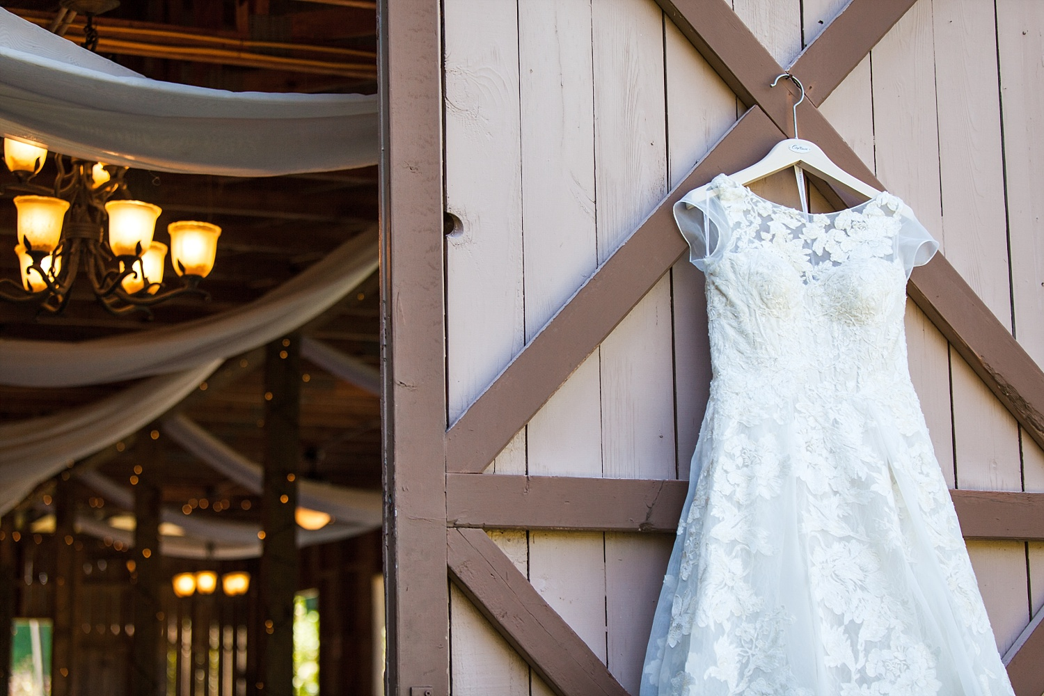 lace wedding dress hanging from barn door at The Fields of Blackberry Cove