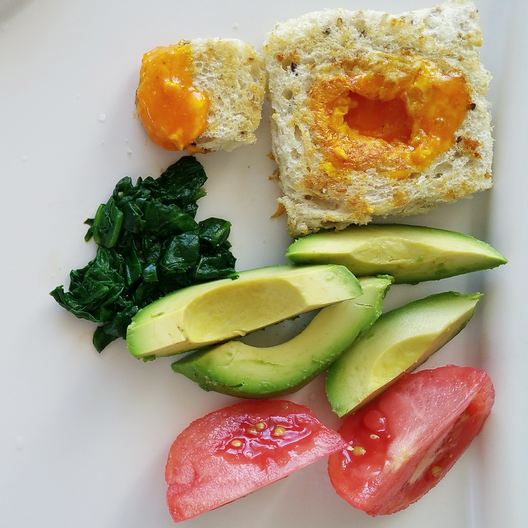 egg yolk in the poke, chopped cooked spinach, avocado, tomato