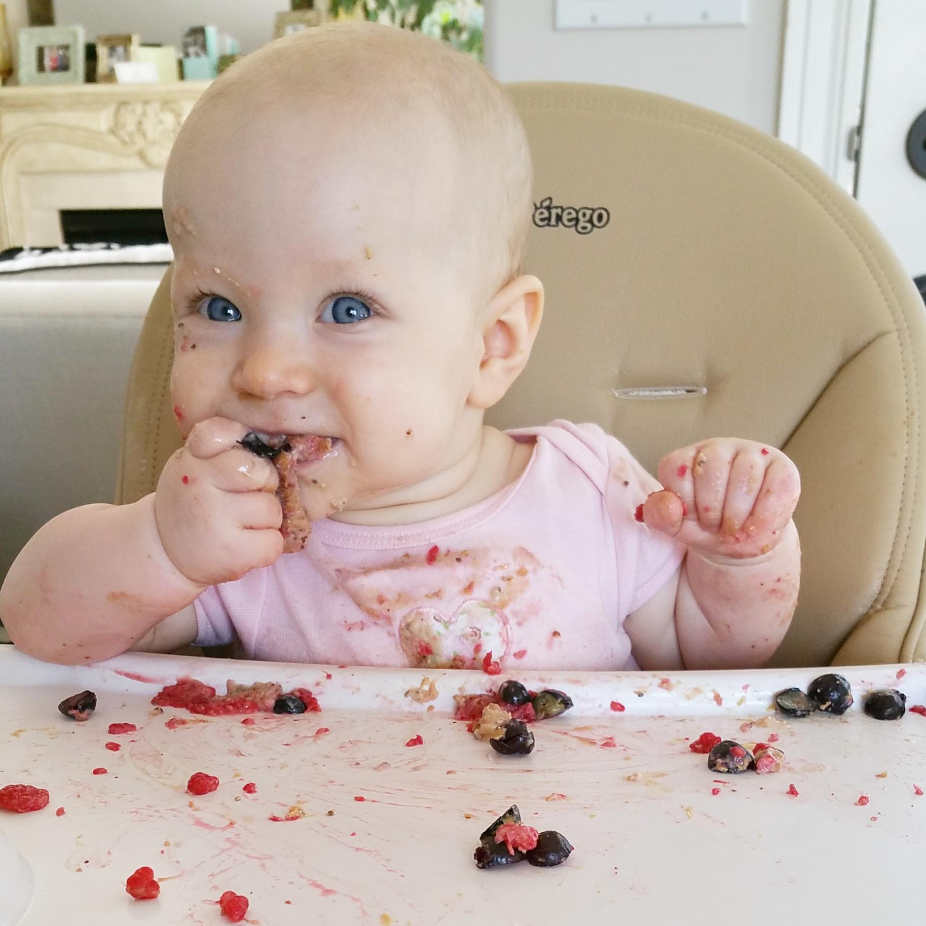 messy baby eating berries