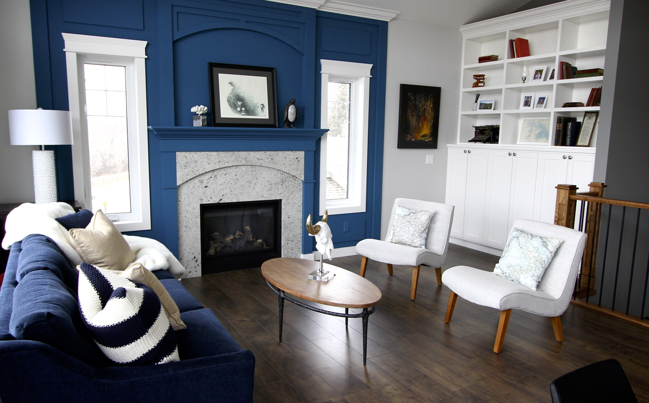 This new-home build features a large open concept main level. To create a focal point and bring the expansive scale in our Designer painted out the fireplace surrounding and trim in a bold blue tone. The finished result is a gorgeous statement that brings the space closer in, creating an inviting environment.