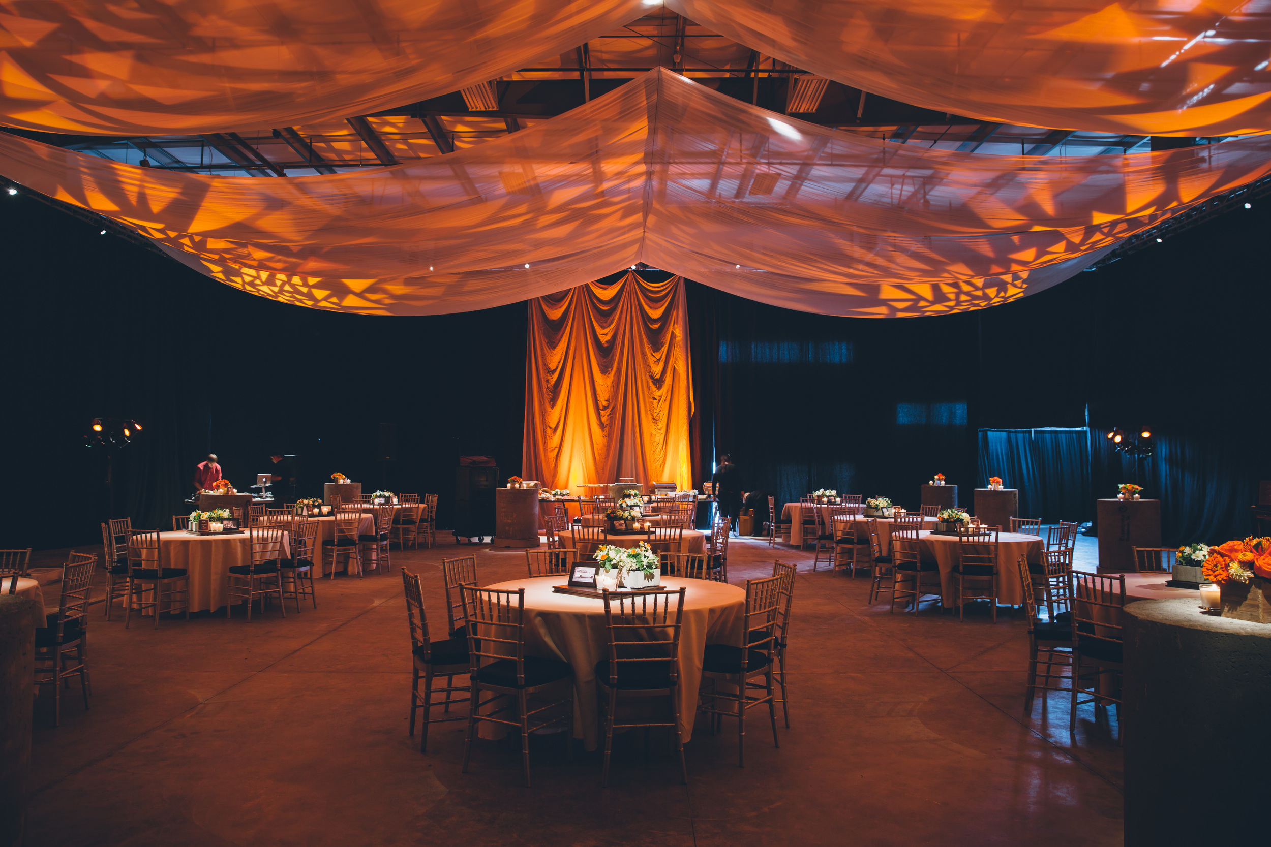 Here we have spot lighting on every table, uplighting on the draping and a pattern on the ceiling for interest. It's amazing what lighting can do to a space!