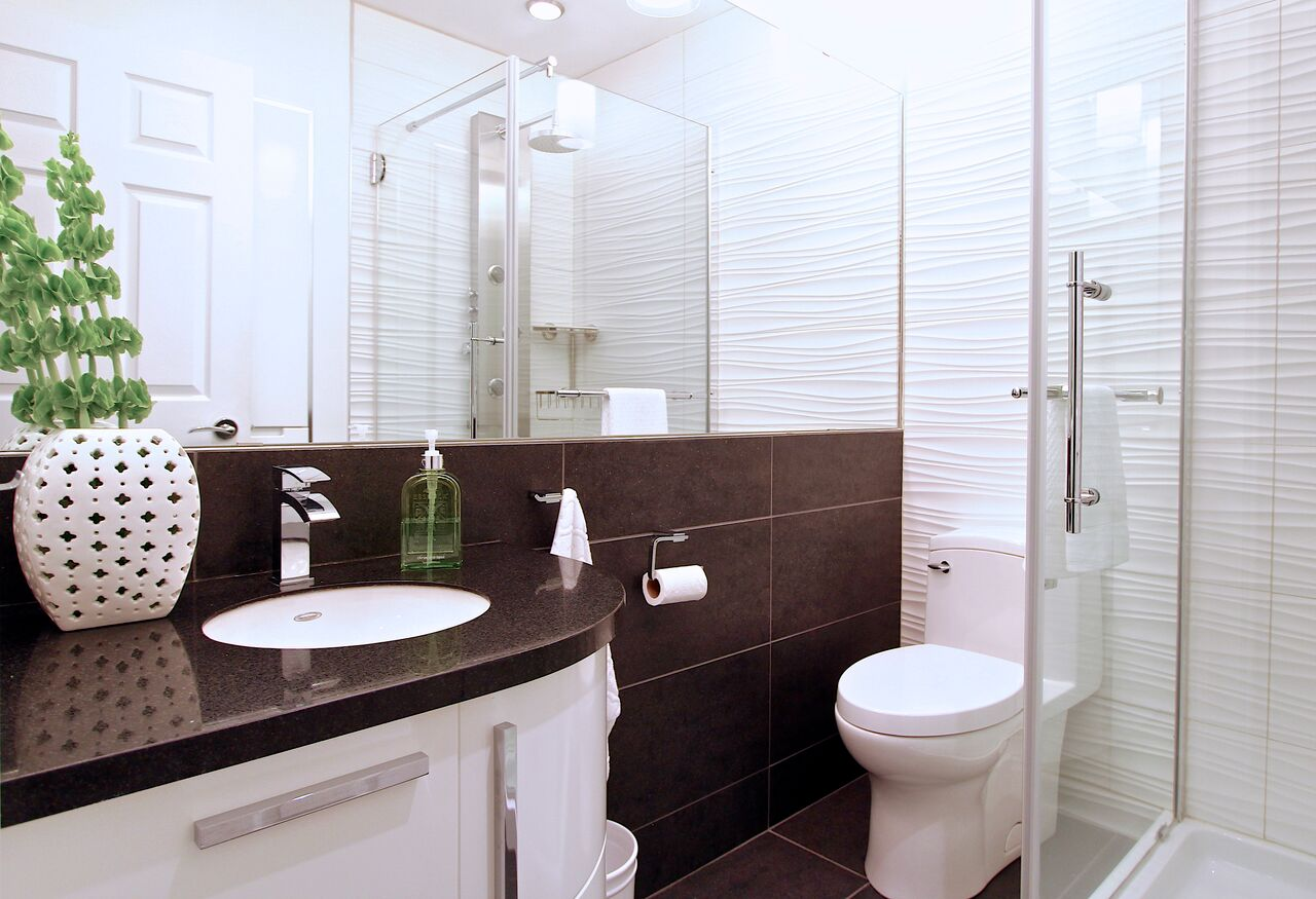 To make make the most of this small bathroom we completely renovated the area and created depth and the illusion of space with a full mirror wall, large scale tile in contrasting tones, glass shower enclosure, and bright white tile in a linear pattern to draw the eye around the room.