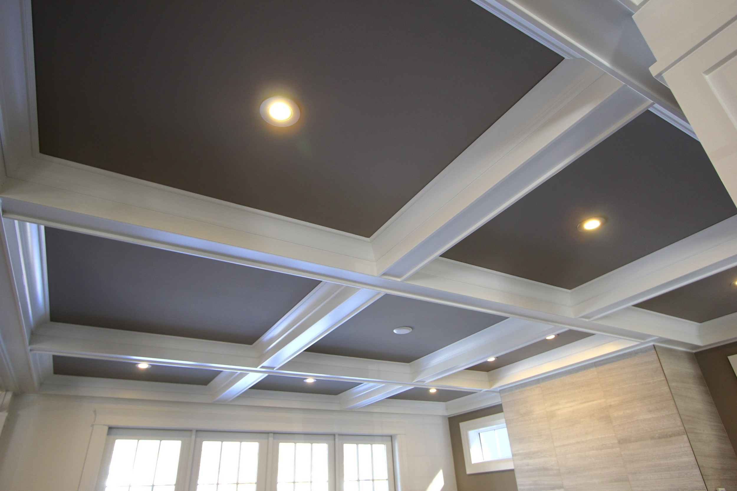 Features don't have to just go on the wall, this coffered ceiling designed by metric is a stunning architectural detail that adds a classic element to the space. The contrasting colors of the ceiling highlight the grid pattern.