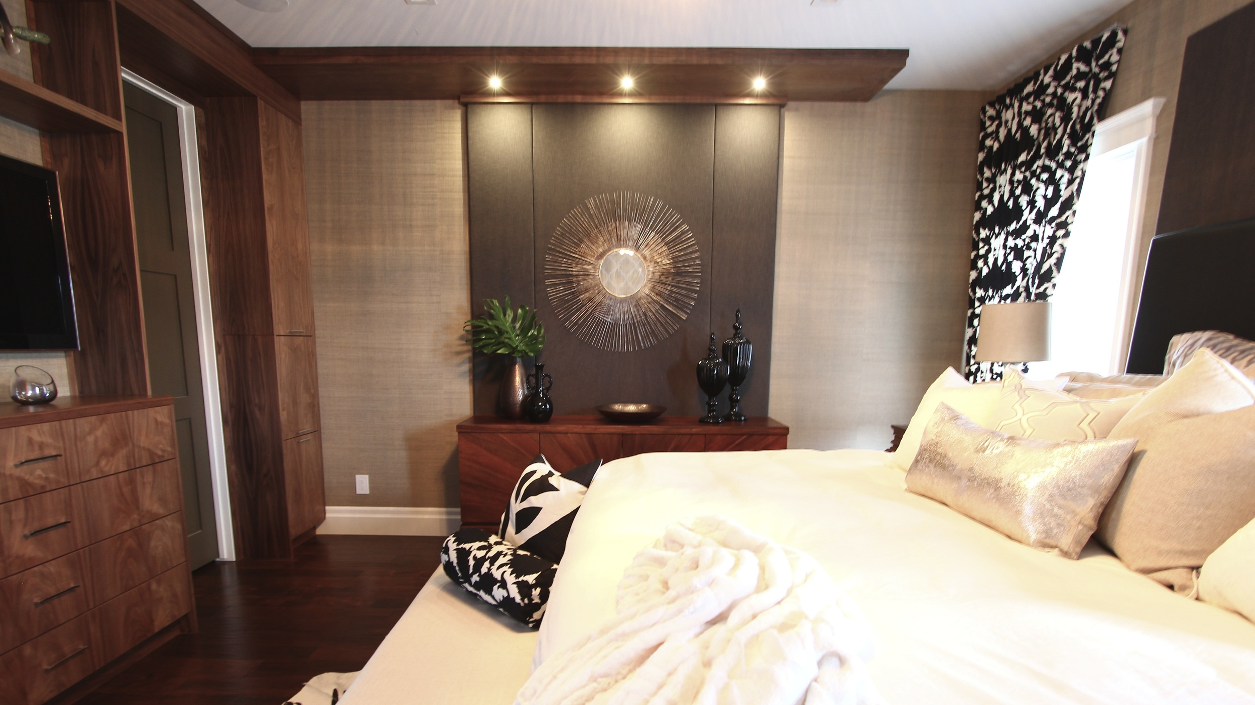 This bedroom design is layered with interesting textures, colors, and materials. Recessed lighting highlight the custom cabinetry and wall-coverings and draw the eye around the space.