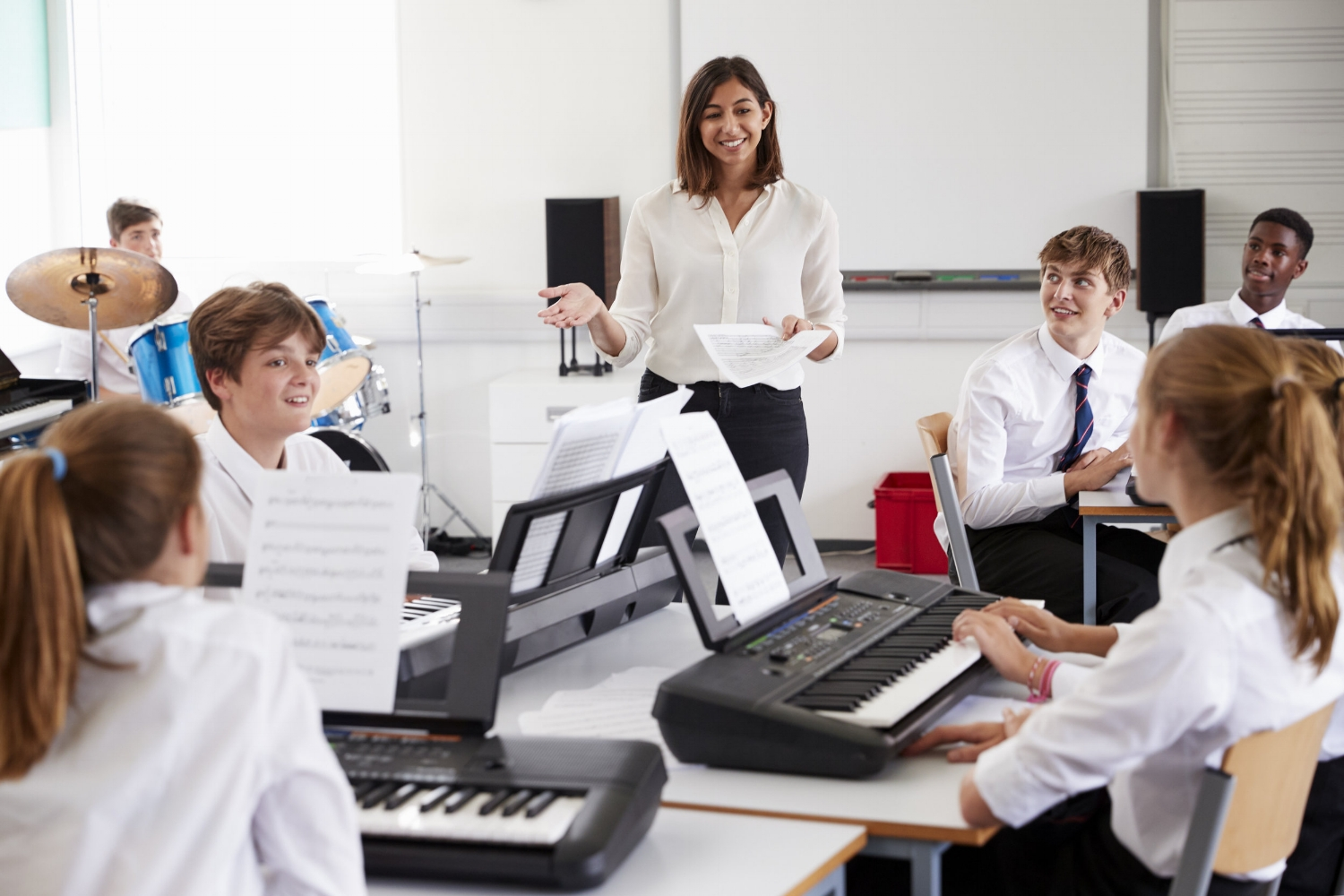Teenage Students Studying Electronic Keyboard In Music Class