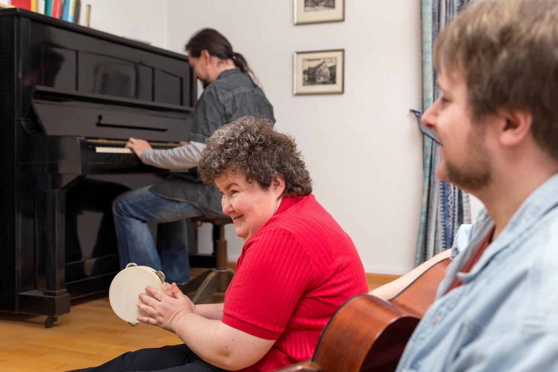 Geistig behinderte Frau mit Betreuern beim musizieren