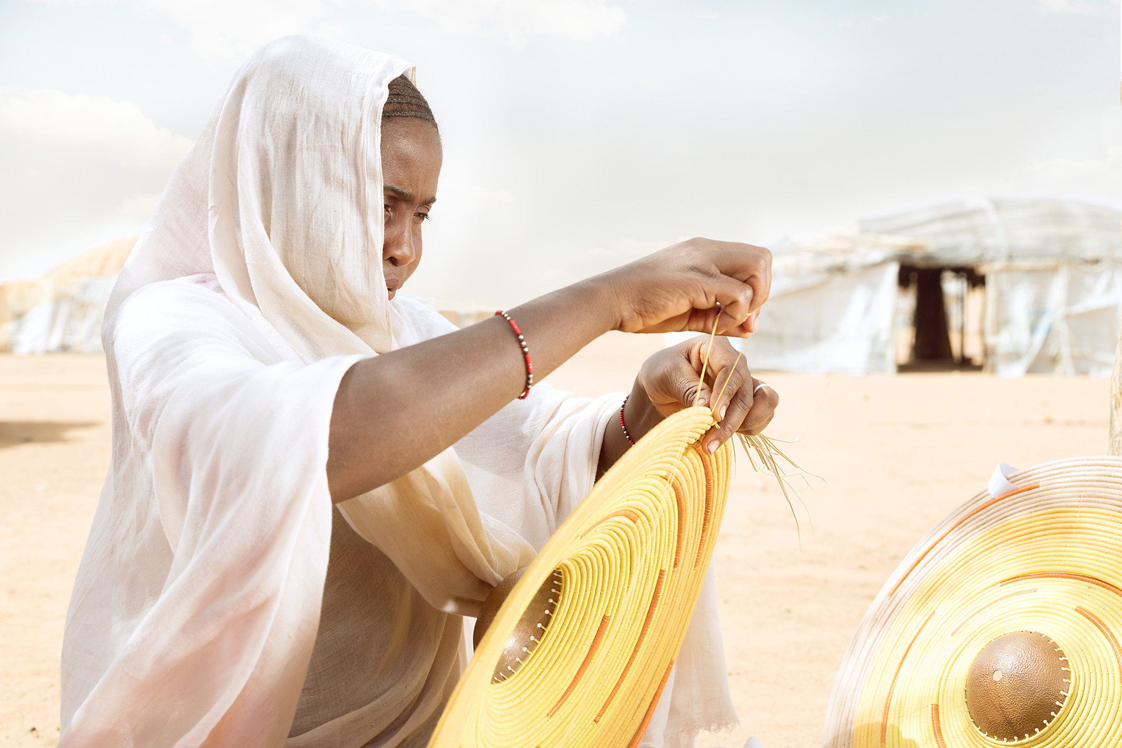 - 'Weaving for Change' reflects the preservation of an old age artisan trade of the Tuareg community from Northern Mali of whom some are living as refugees in Burkina Faso. Behind every handcrafted lamp you will find the Tuareg heritage. The design combines unique artisanal skills and basketry techniques carried out by Tuareg and Fulani/ Peulh women. Through creative collaborations such as these the refugee artisans living in extreme poverty may have an opportunity to change their lives. This collaboration also aligns with A A K S' brand values of ethical production.We invite you to visit our blog to discover more about the making process.