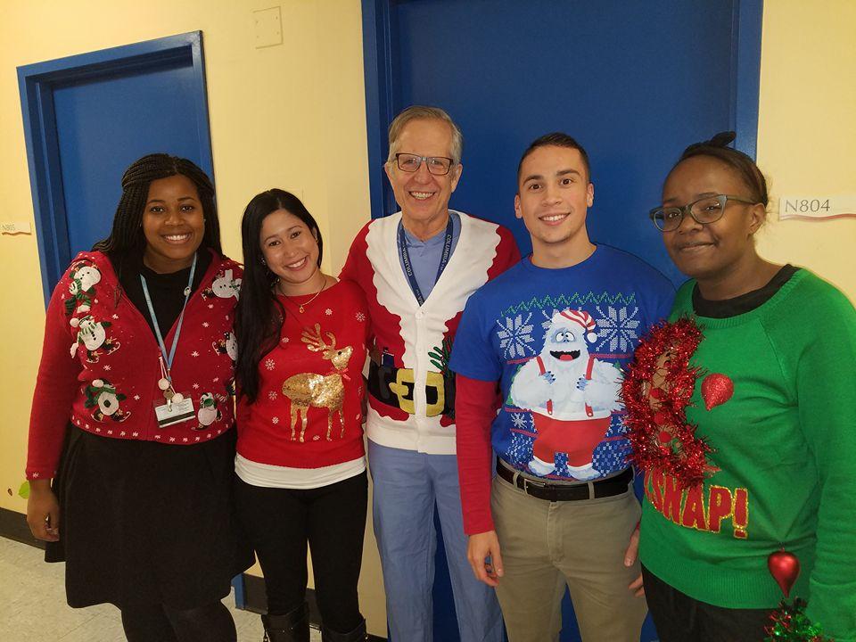 """按照惯例,每年圣诞节放假的前一天整个科室都要穿着""""圣诞丑毛衣""""上班。今年的那天我刚从手术室出来,就被套上了毛衣跟科室同事们合照。照片中的右二就是我的行政助理乔纳森(Jonathan),右一是我们科室的医疗助理Tiara,另外两位女士同样是我们科室的行政人员。"""
