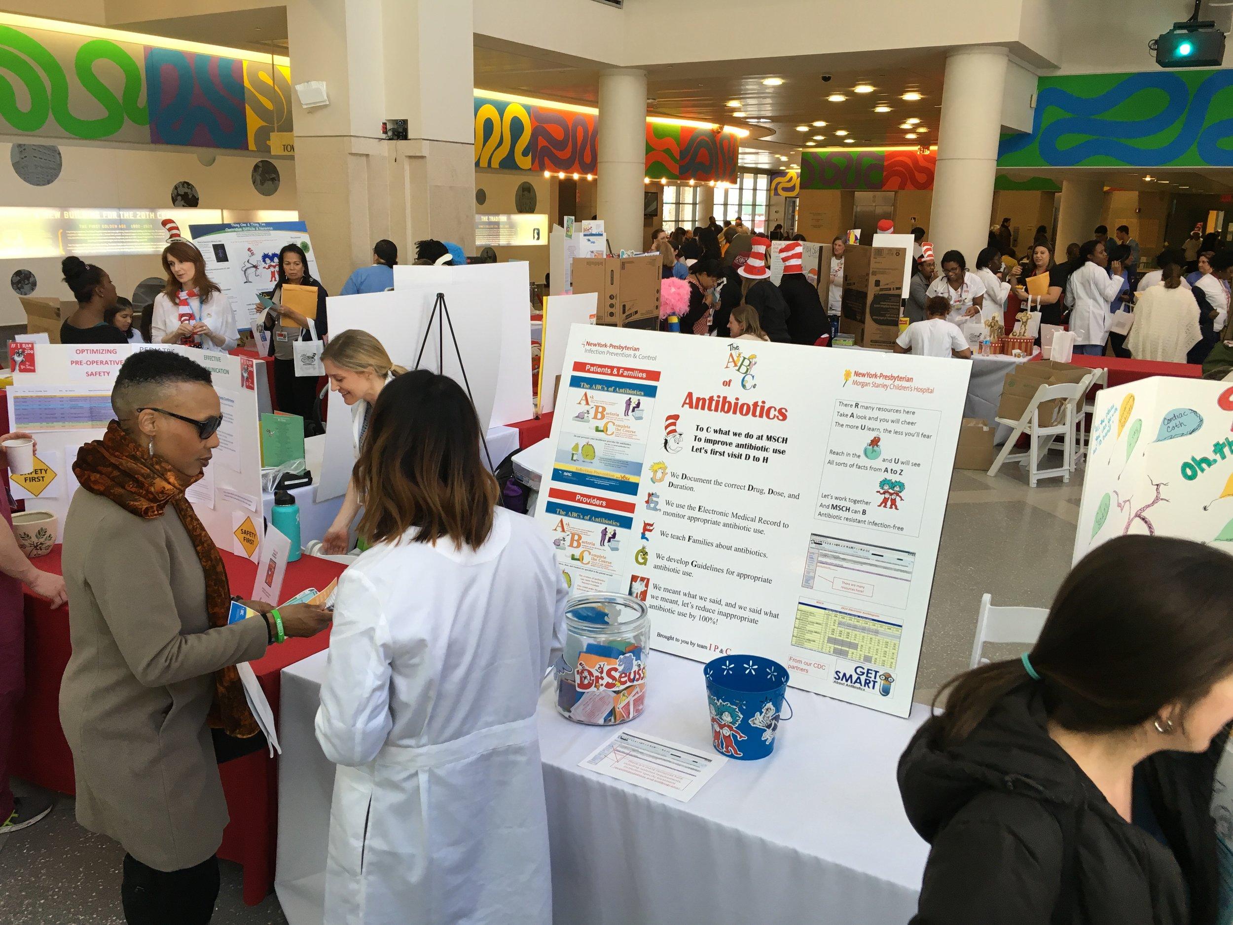 ▲周一在儿童医院大堂举办的患者安全展会。镜头正中是一个介绍抗生素使用的摊位游戏,医生正在与以为病人家长交流。会场内一共有20多个这种摊位,分别介绍不同的患者安全知识。