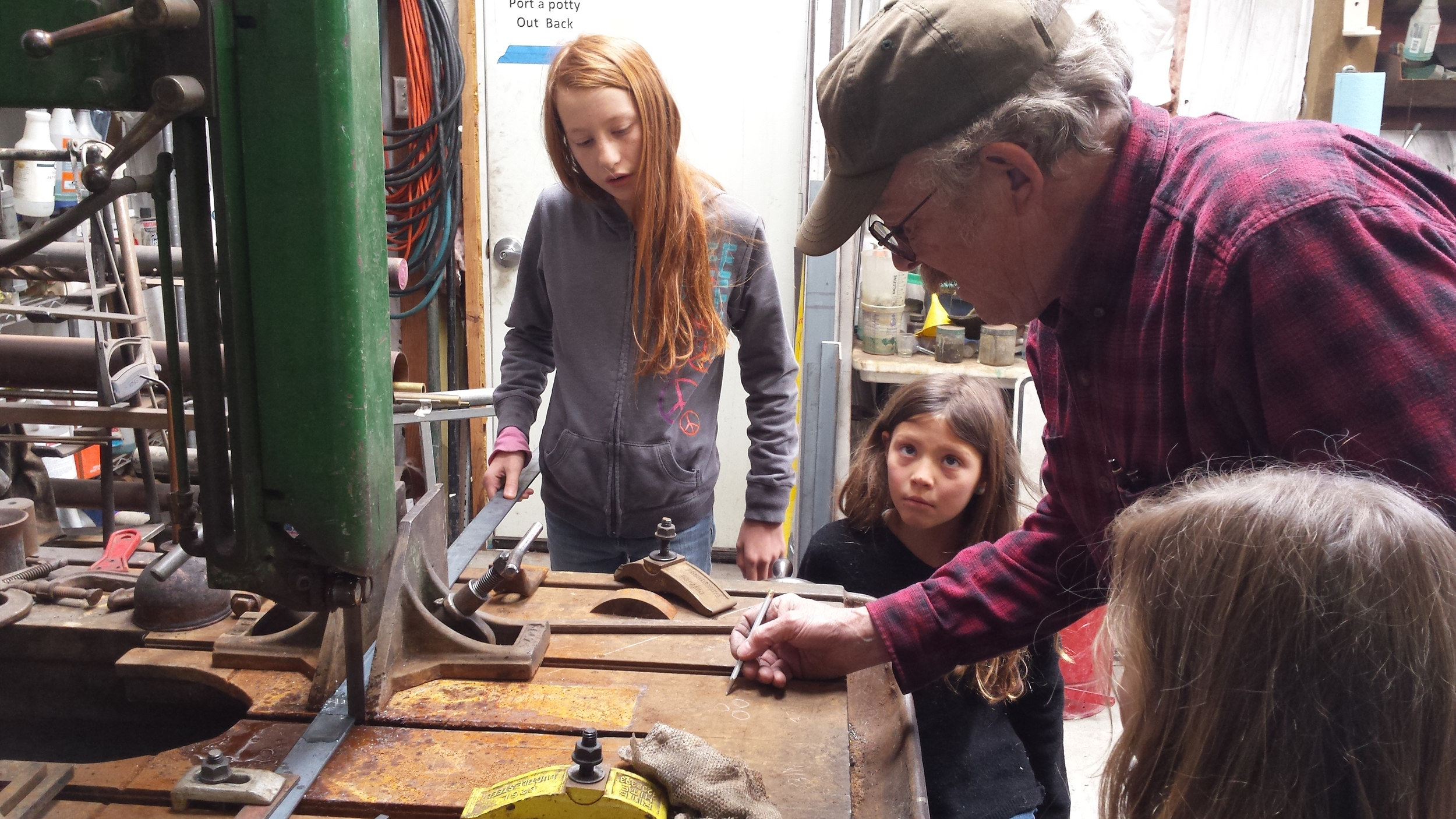 The girls learning about measuring and cutting steel.