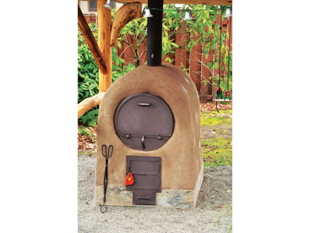 A barrel oven pictured in the book, finished with cob plaster.