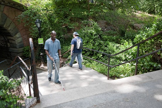 Romeo Edmead walks in Central Park with a help of a cane.