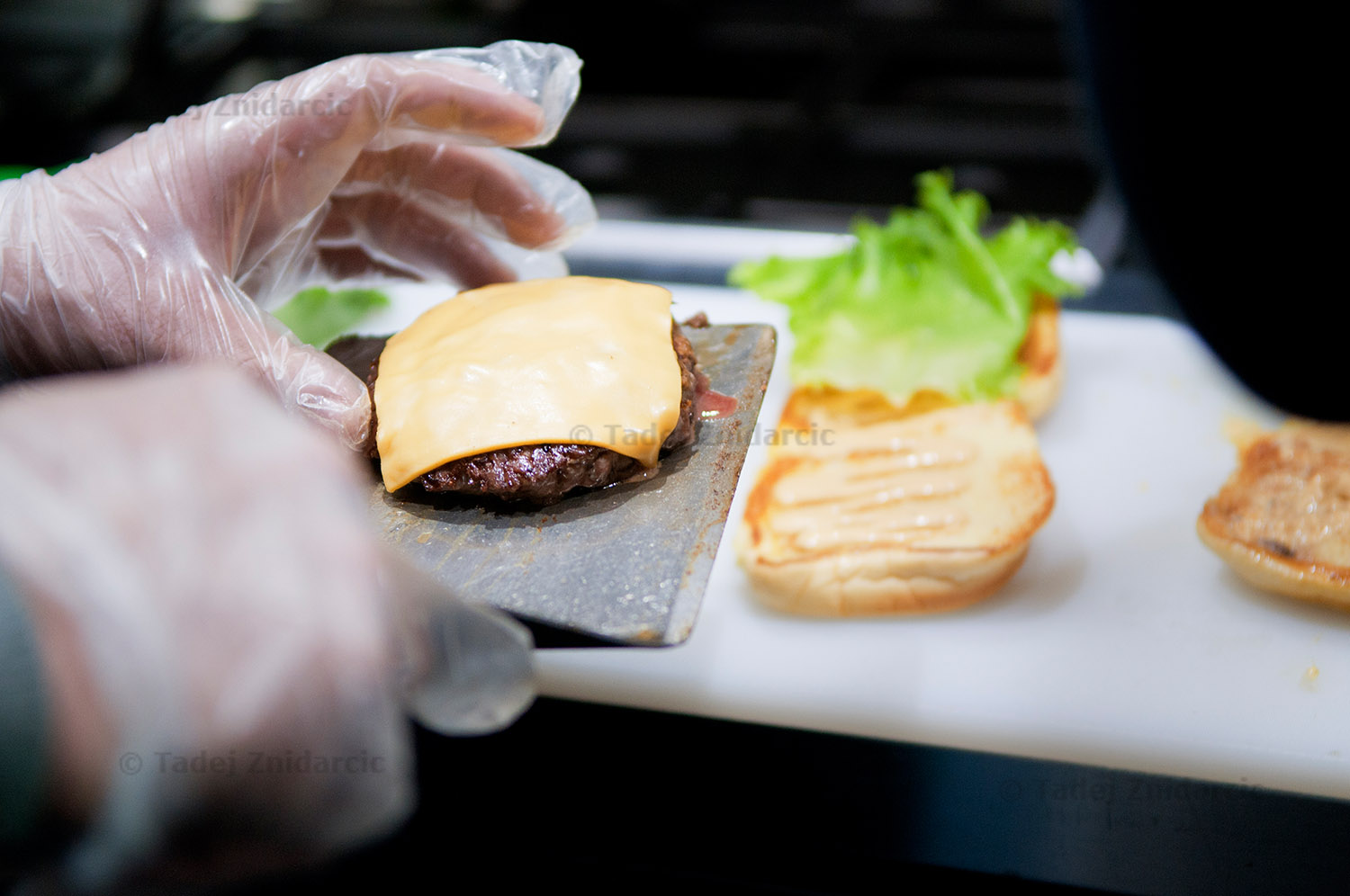 Cook prepares a burger at Burger Heights on Wadsworth Ave.